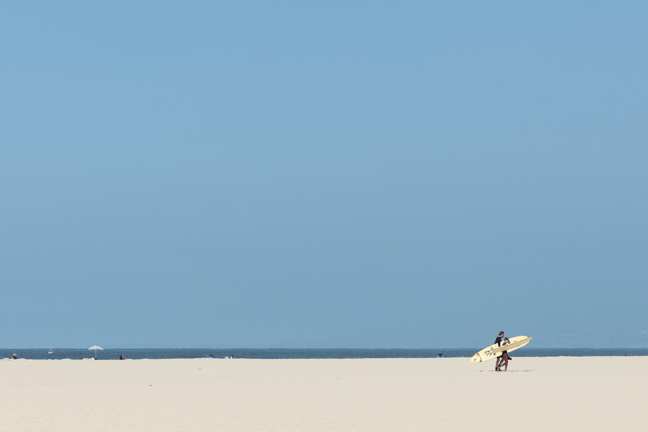 Surfer walking on the beach with a long board. Kimberly Genevieve lifestyle photographer Los Angeles