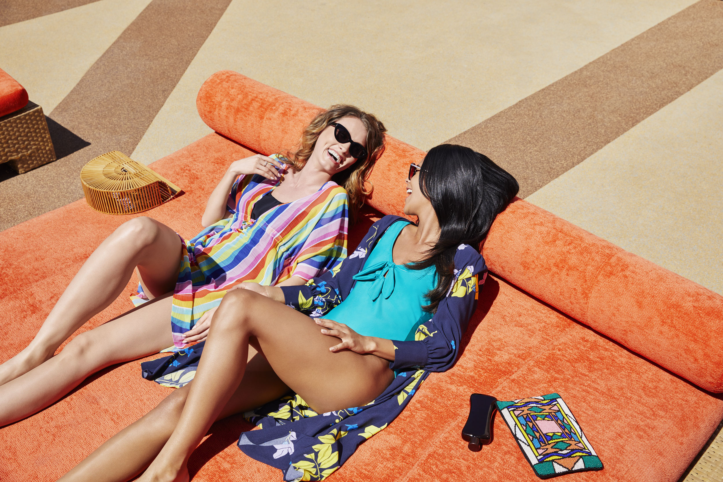 Two girls on vacation in swimsuits and coverups laying on a daybed