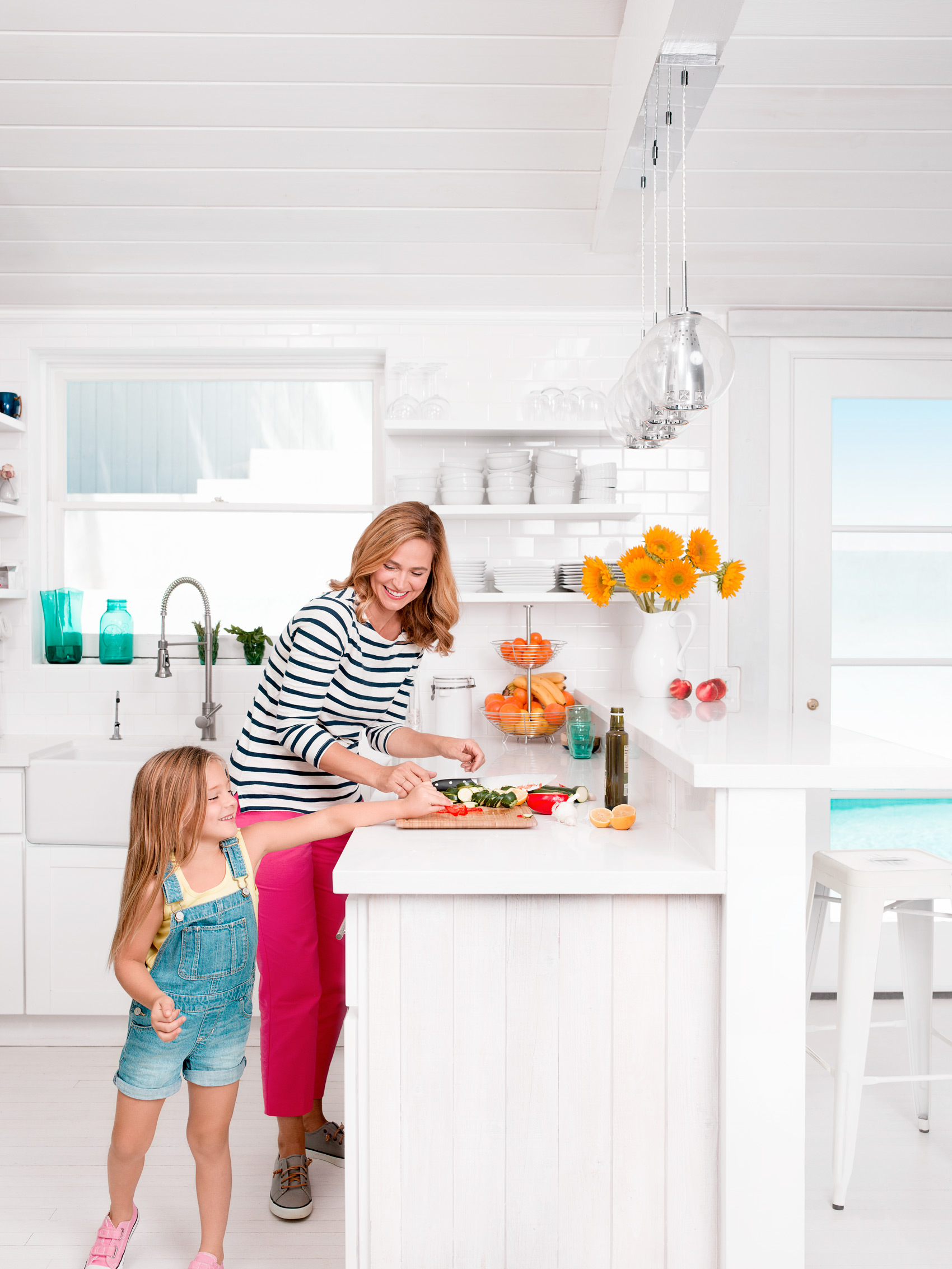 Daughter trying to sneak food while cooking with mom - Kimberly Genevieve Los Angeles Lifestyle Advertising Photographer