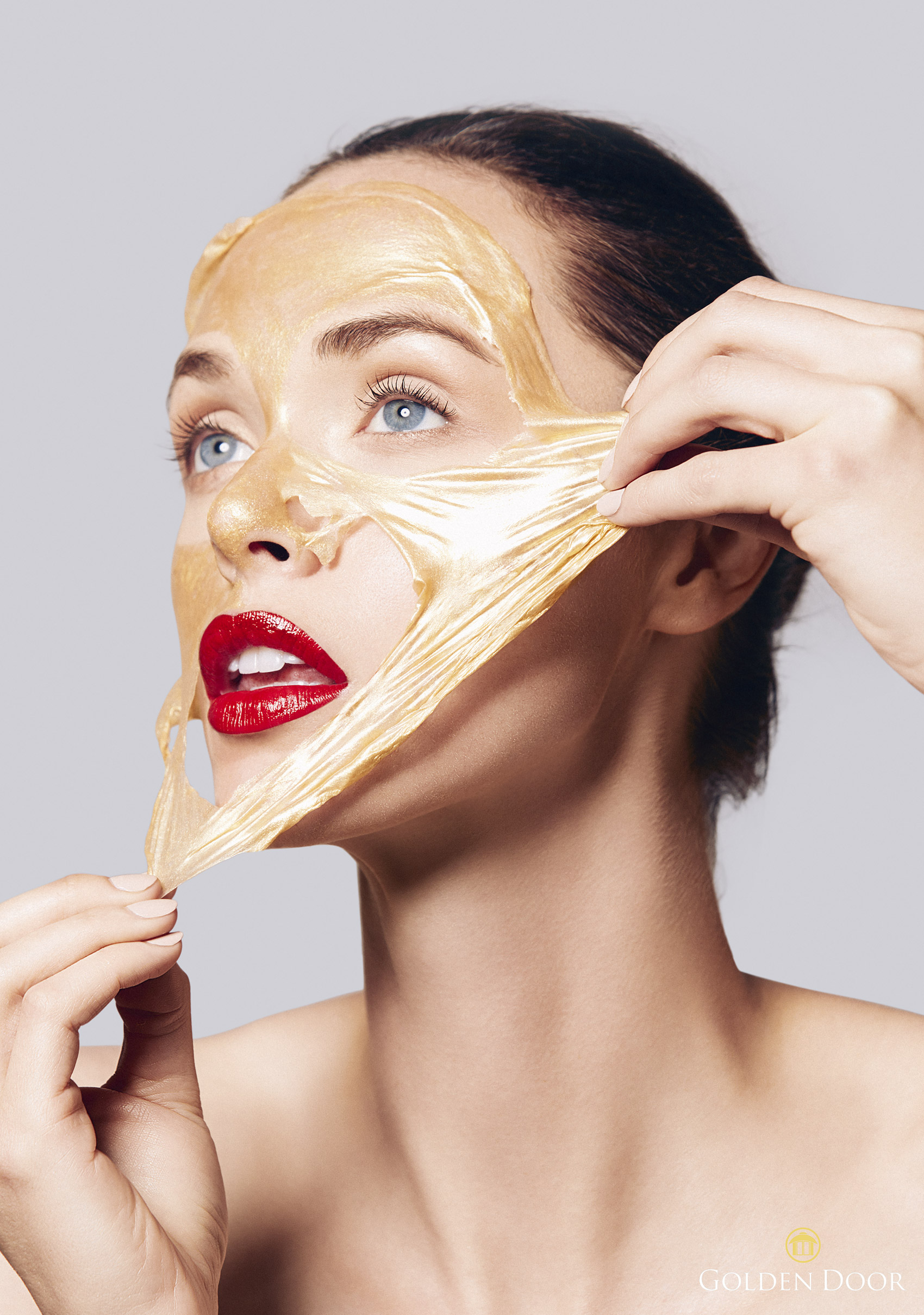 Girl wearing red lipstick peeling off a gold face mask - Kimberly Genevieve Los Angeles Lifestyle Advertising Photographer