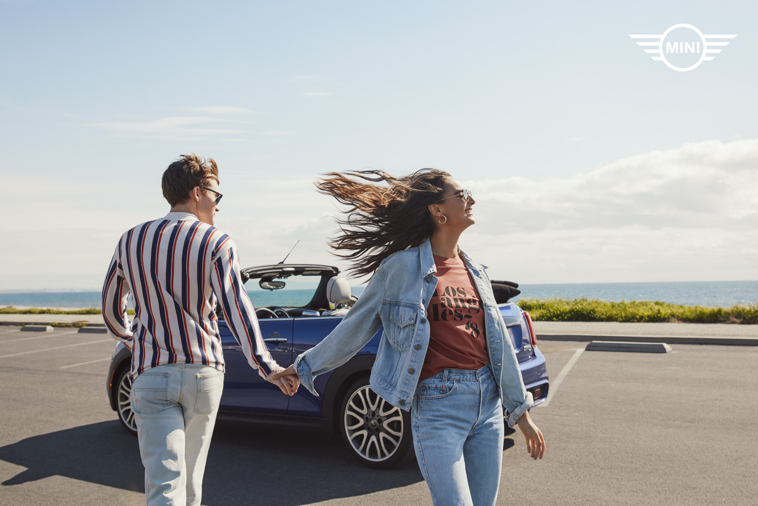 Millennials holding hands walking to a convertible at the beach - Kimberly Genevieve Los Angeles Advertising Photographer