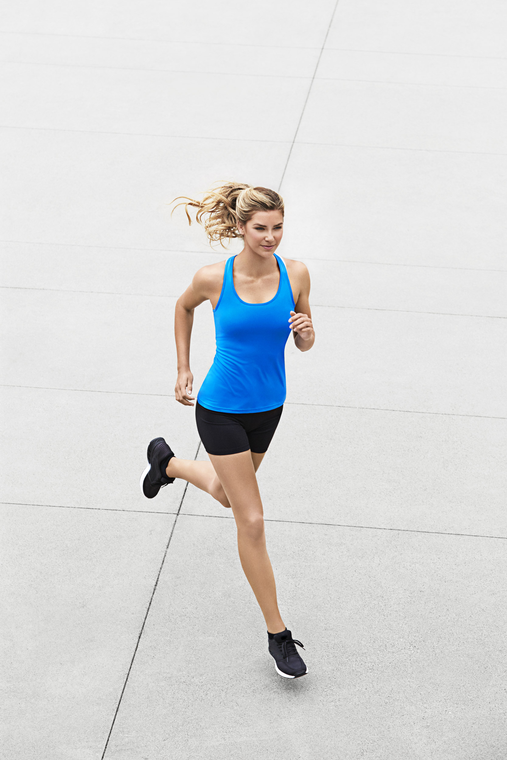 Woman in exercise clothes and a ponytail running in the street - Kimberly Genevieve Los Angeles Lifestyle Advertising Photographer