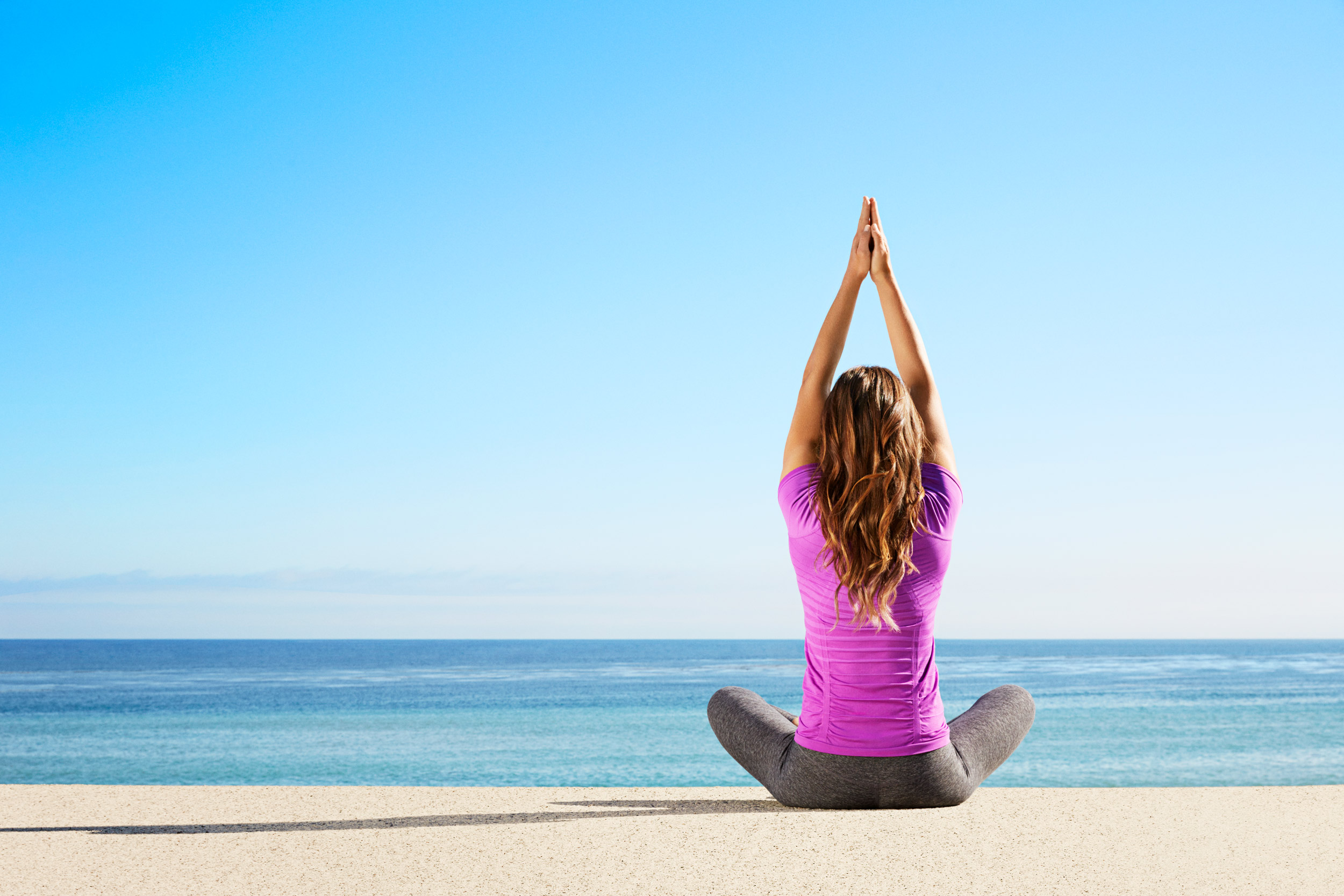 Woman in exercise clothes doing yoga outdoors near the ocean