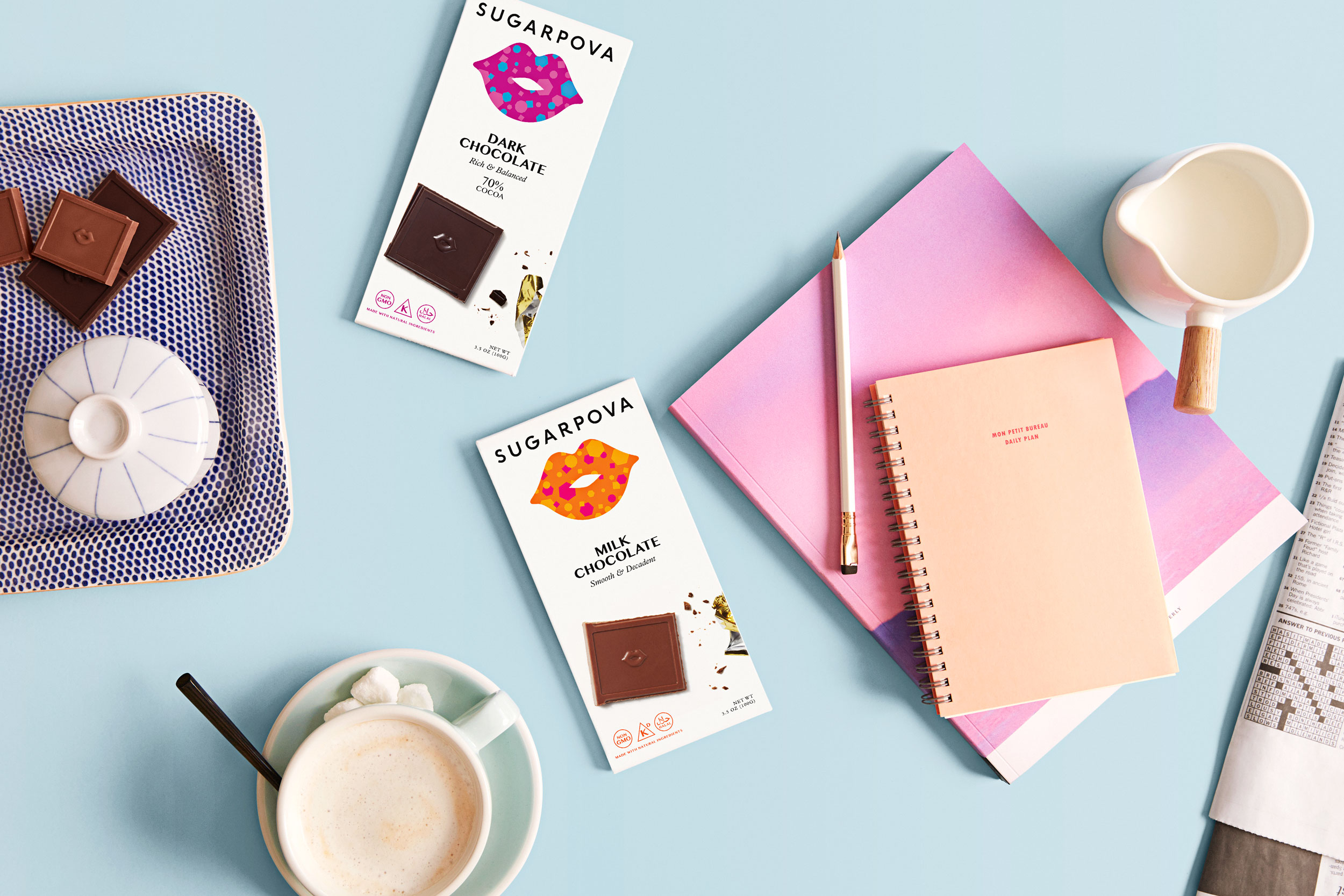 Chocolate bars, notebooks and coffee on a blue table - Kimberly Genevieve Los Angeles Lifestyle Advertising Photographer