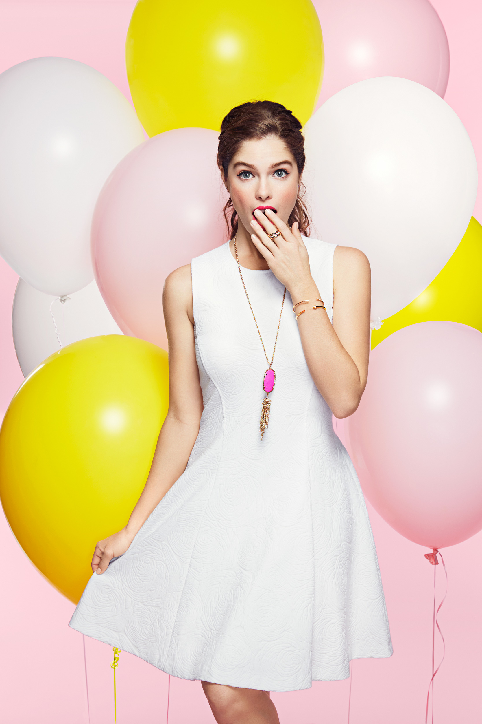 Girl standing with balloons wearing a white dress