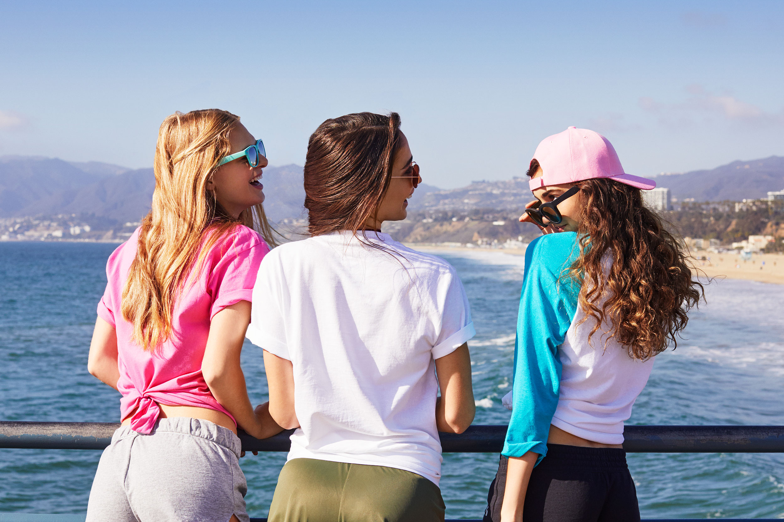 Girls laughing together on a pier facing the ocean - Kim Genevieve Los Angeles Lifestyle Photographer