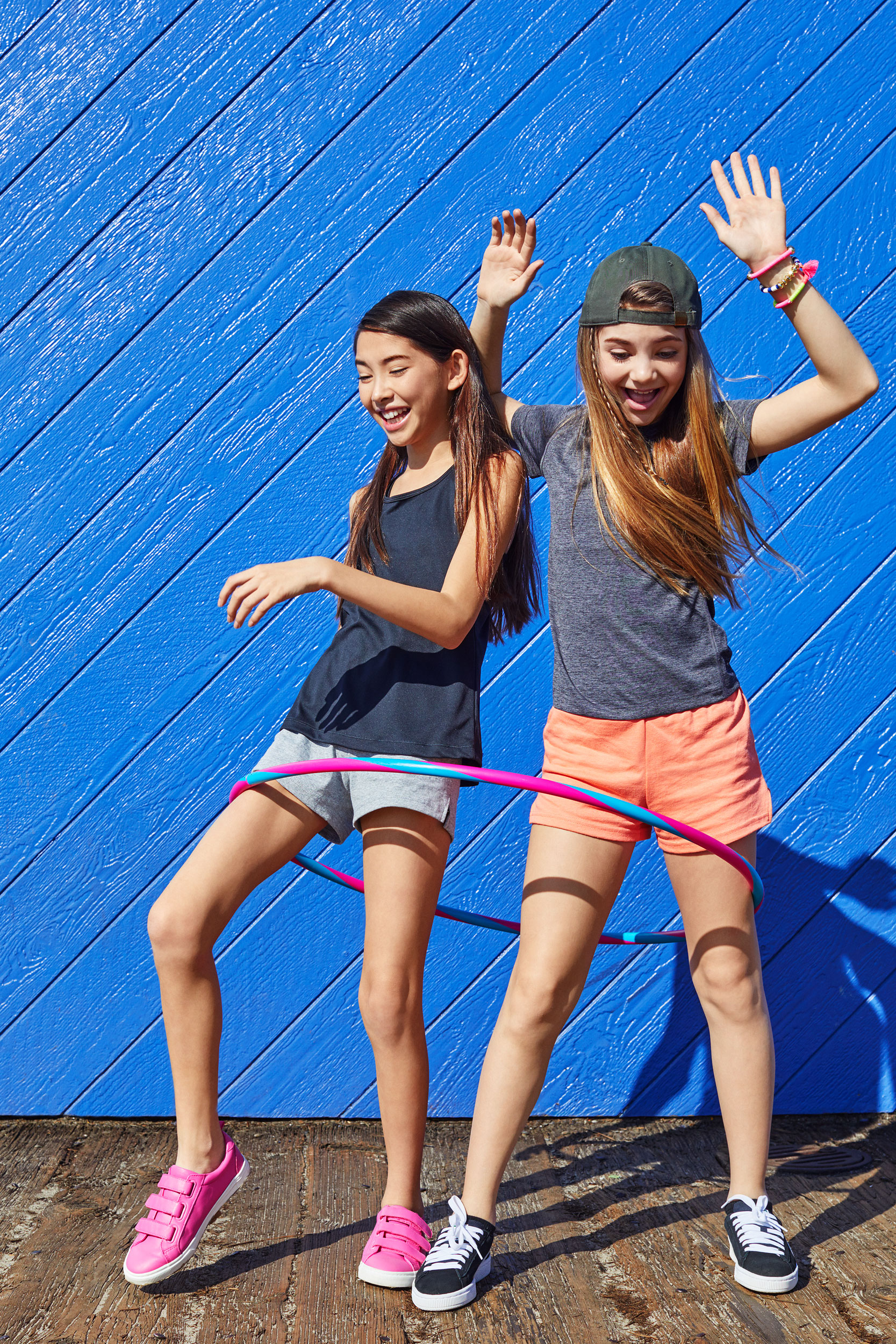 Girls laughing together trying to use one hula hoop - Kim Genevieve Los Angeles Lifestyle Photographer