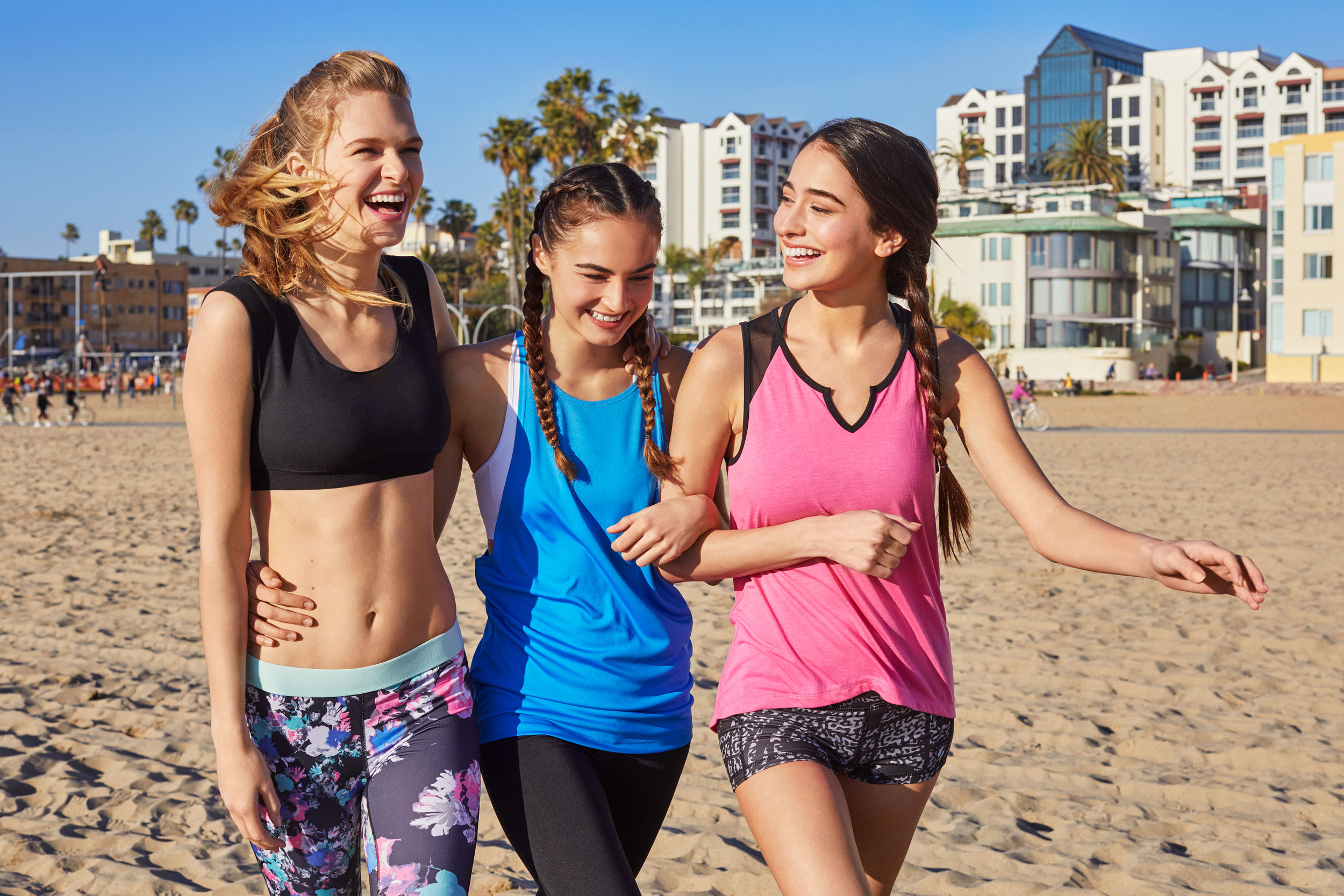 Girls in exercise clothes walking together laughing on the beach - Kim Genevieve Los Angeles Lifestyle Photographer