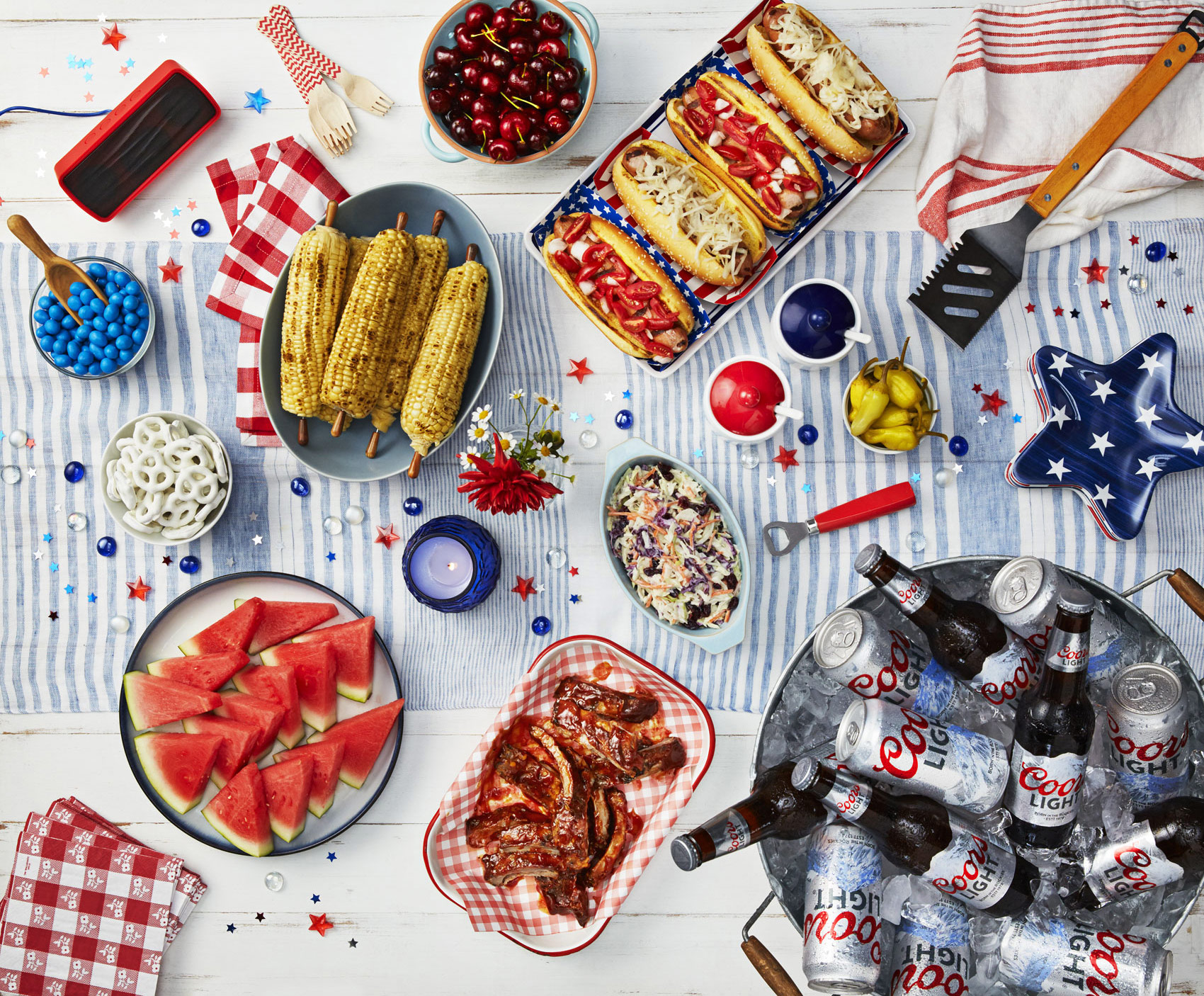 Coors light beer with 4th of July snacks on a picnic table