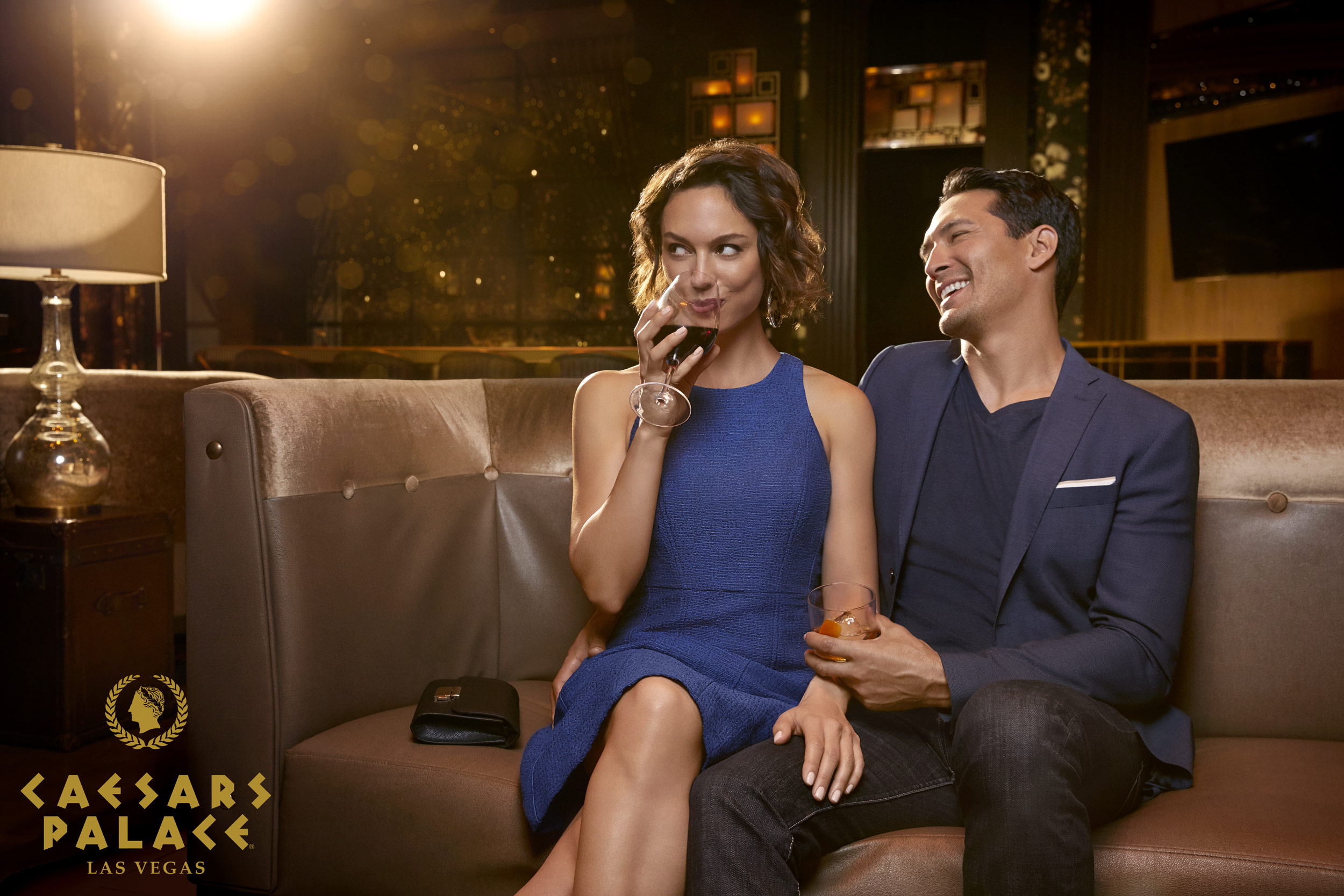 Couple sitting in a lounge drinking wine and laughing - Kimberly Genevieve Los Angeles Lifestyle Advertising Photographer