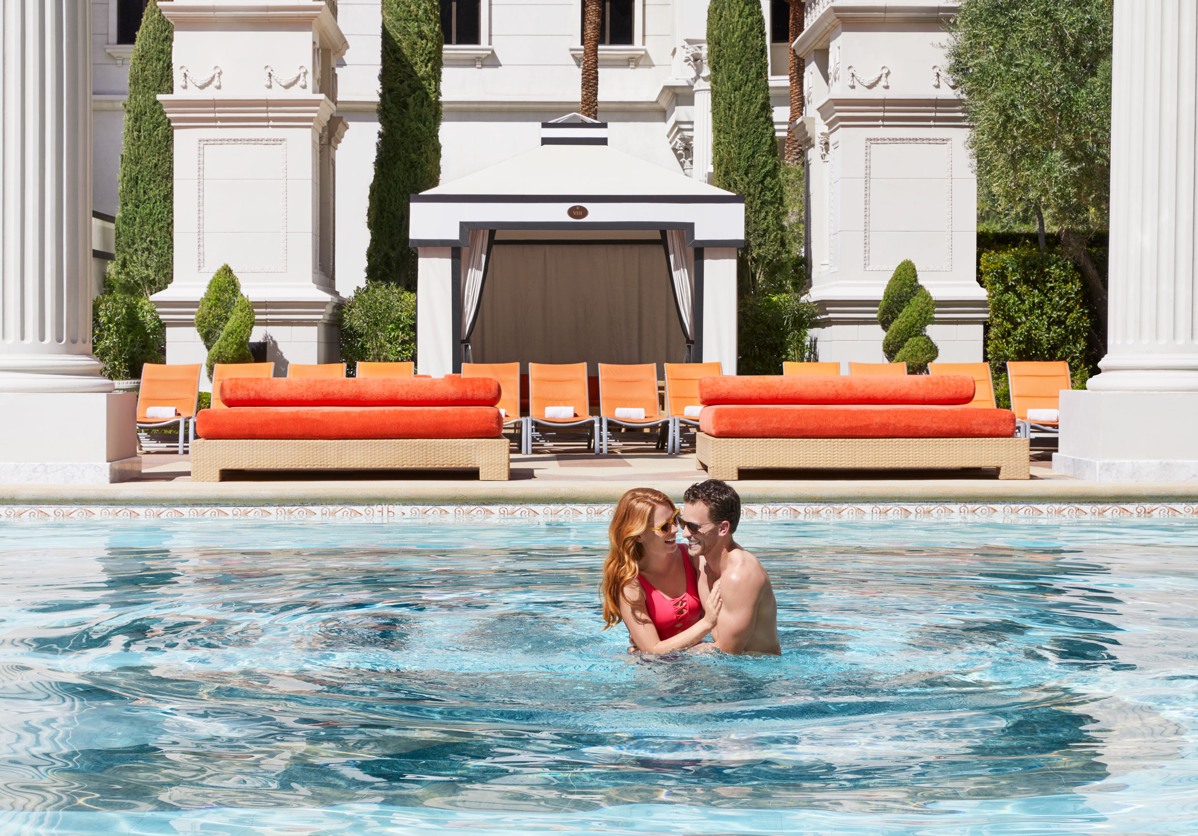 Couple laughing together in a pool on vacation - Kimberly Genevieve Los Angeles Lifestyle Advertising Photographer