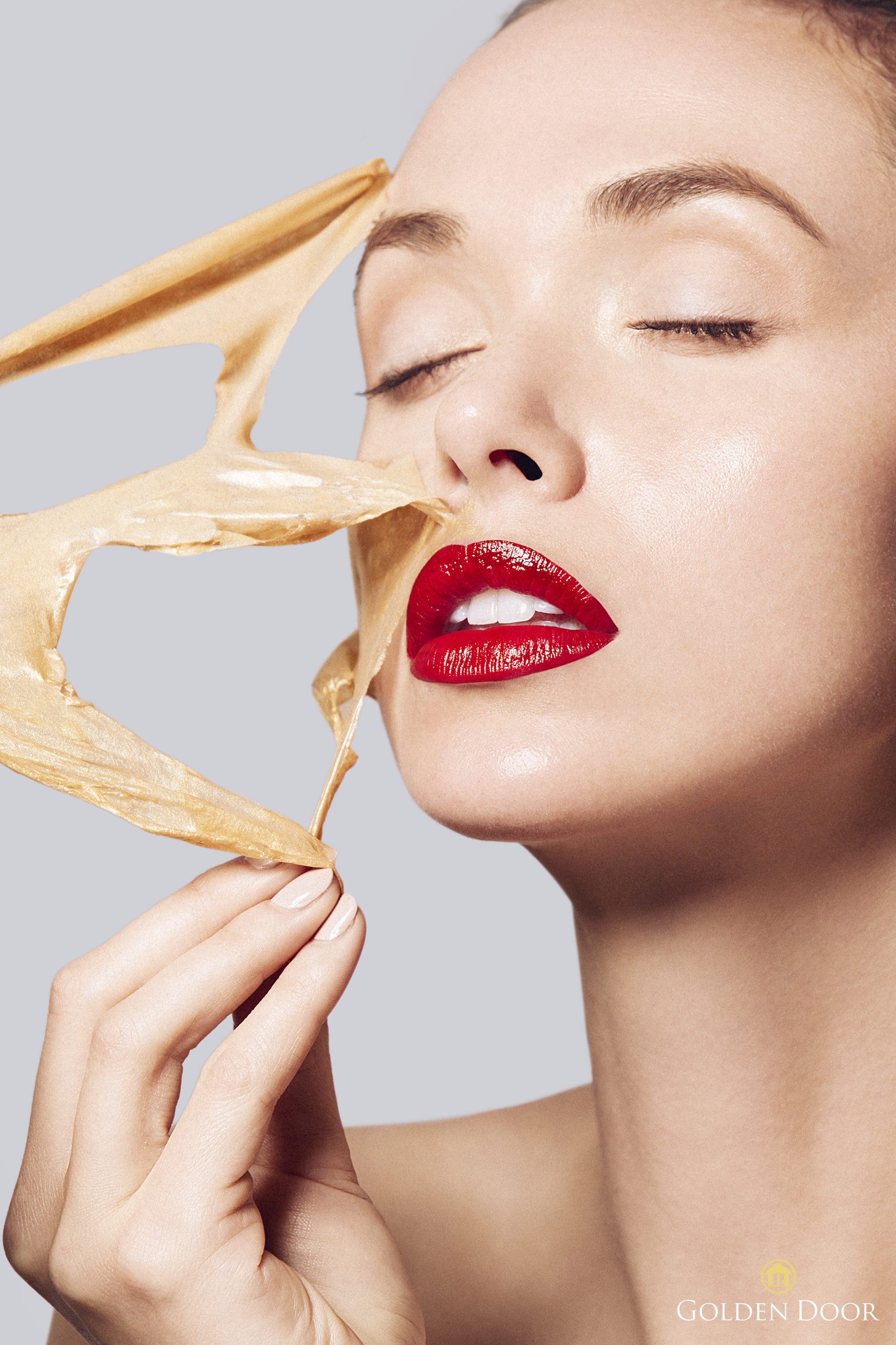 Girl wearing red lipstick peels off a gold face mask - Kimberly Genevieve Los Angeles Lifestyle Advertising Photographer