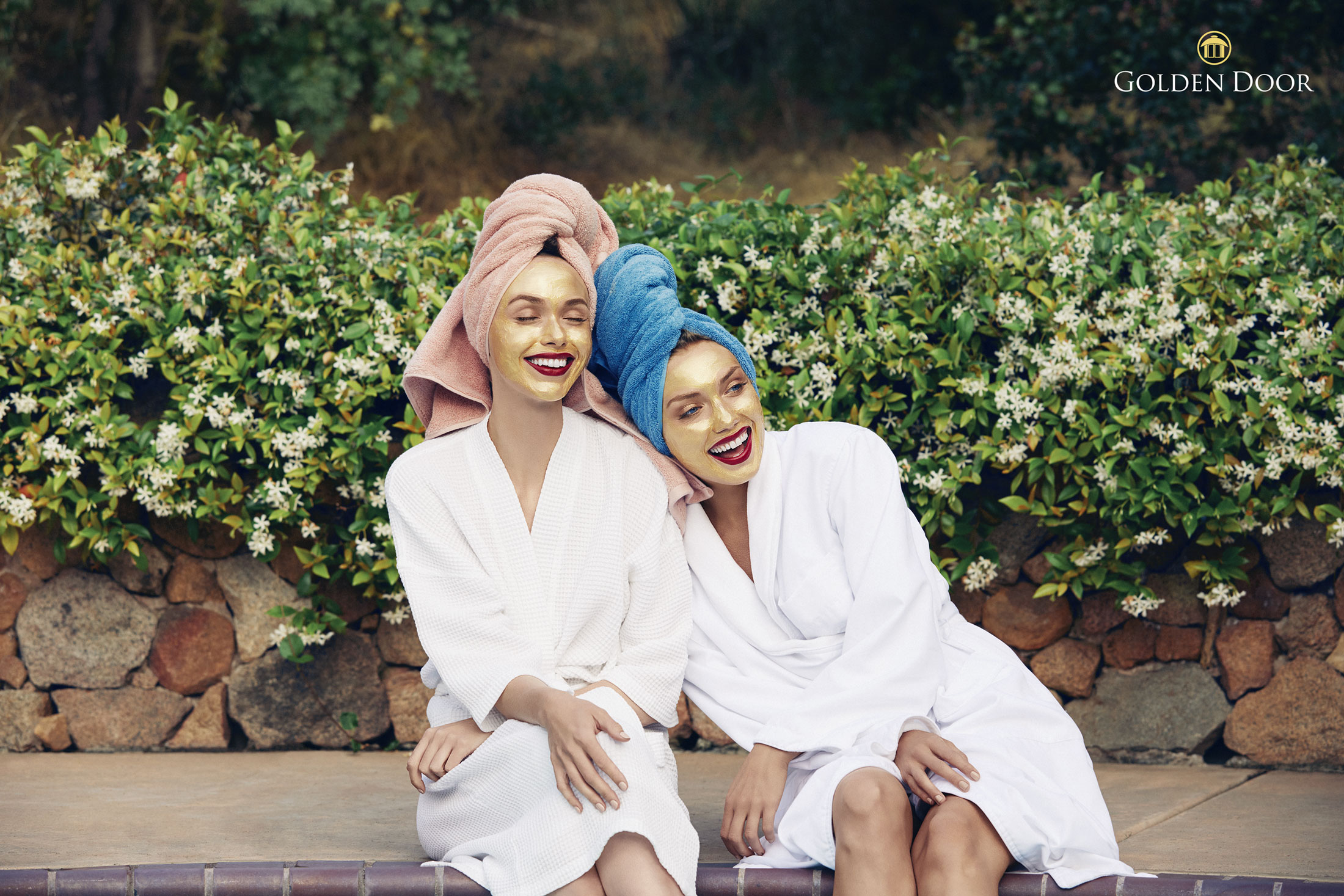 Two girls at a spa with bathrobes in gold facial masks laughing - Kimberly Genevieve Los Angeles Advertising Photographer