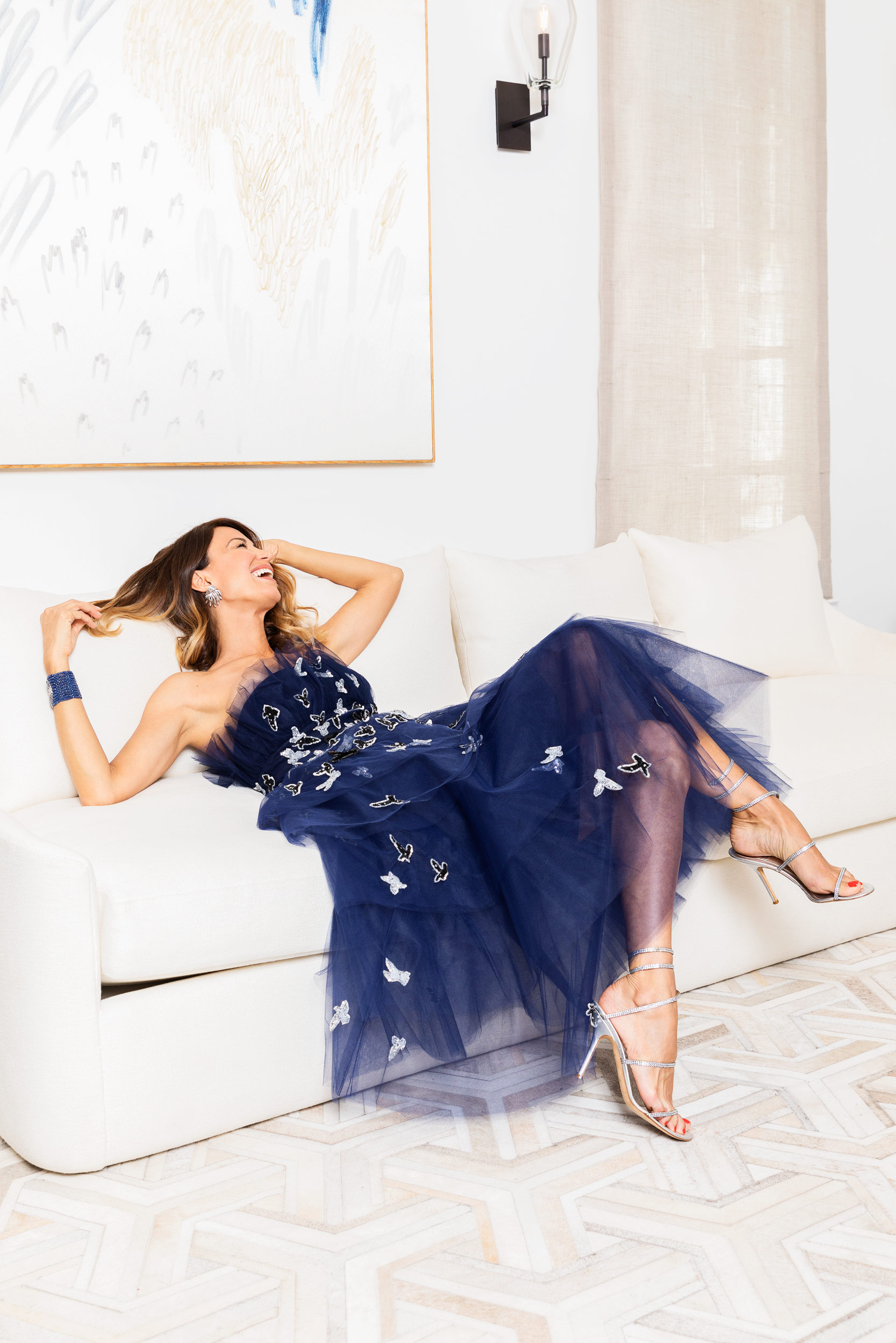 Woman in a Versace Dress laying on a white sofa. Kim Genevieve Los Angeles Portrait Photographer