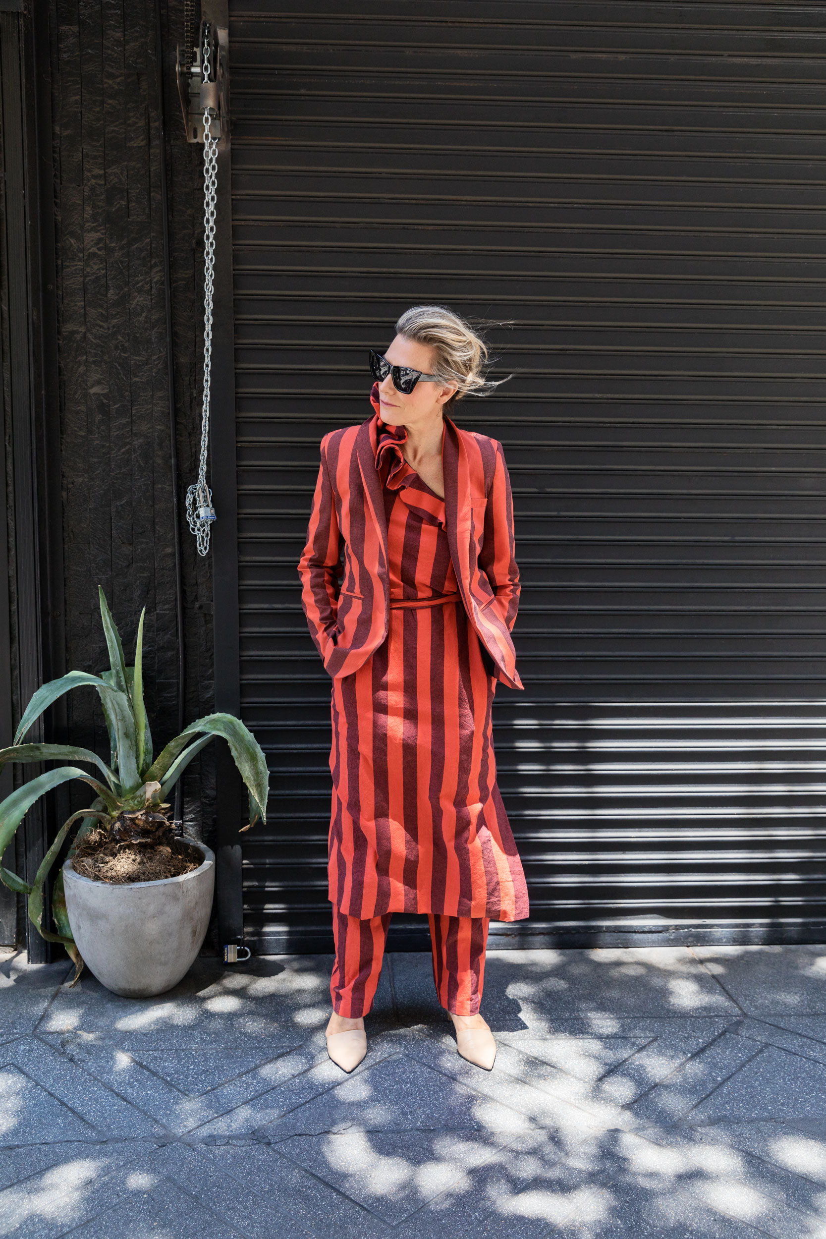 Woman wearing an orange stripped suit on a street sidewalk. Kim Genevieve Los Angeles Portrait Photographer