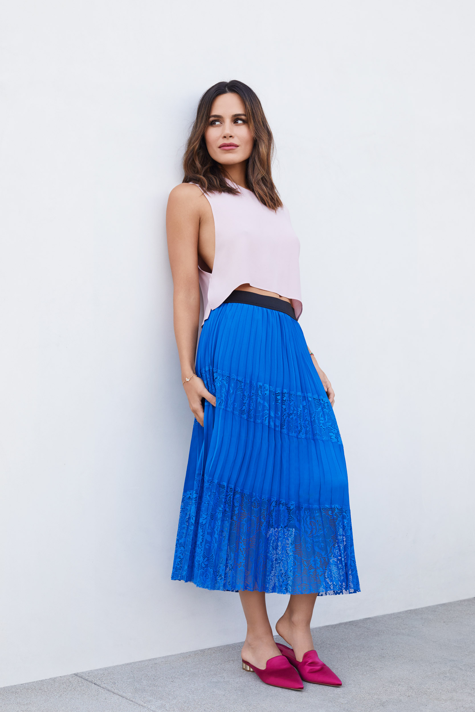 Woman wearing a vibrant blue skirt leaning against a wall