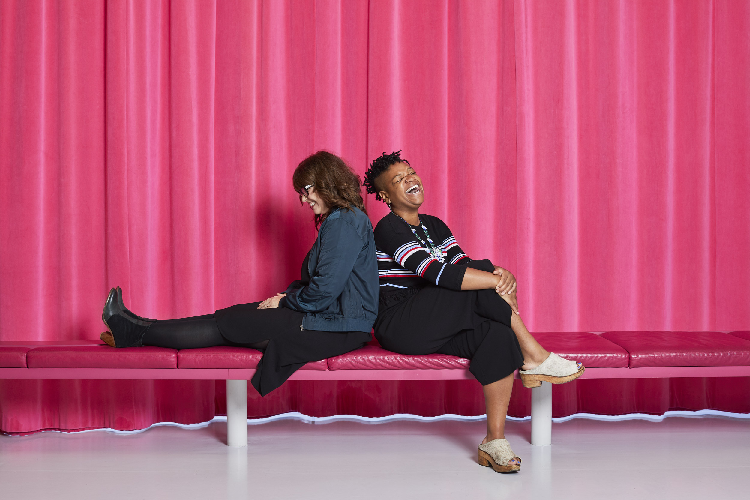 Two women sitting and smiling against a pink curtain. Kim Genevieve Los Angeles Portrait Photographer