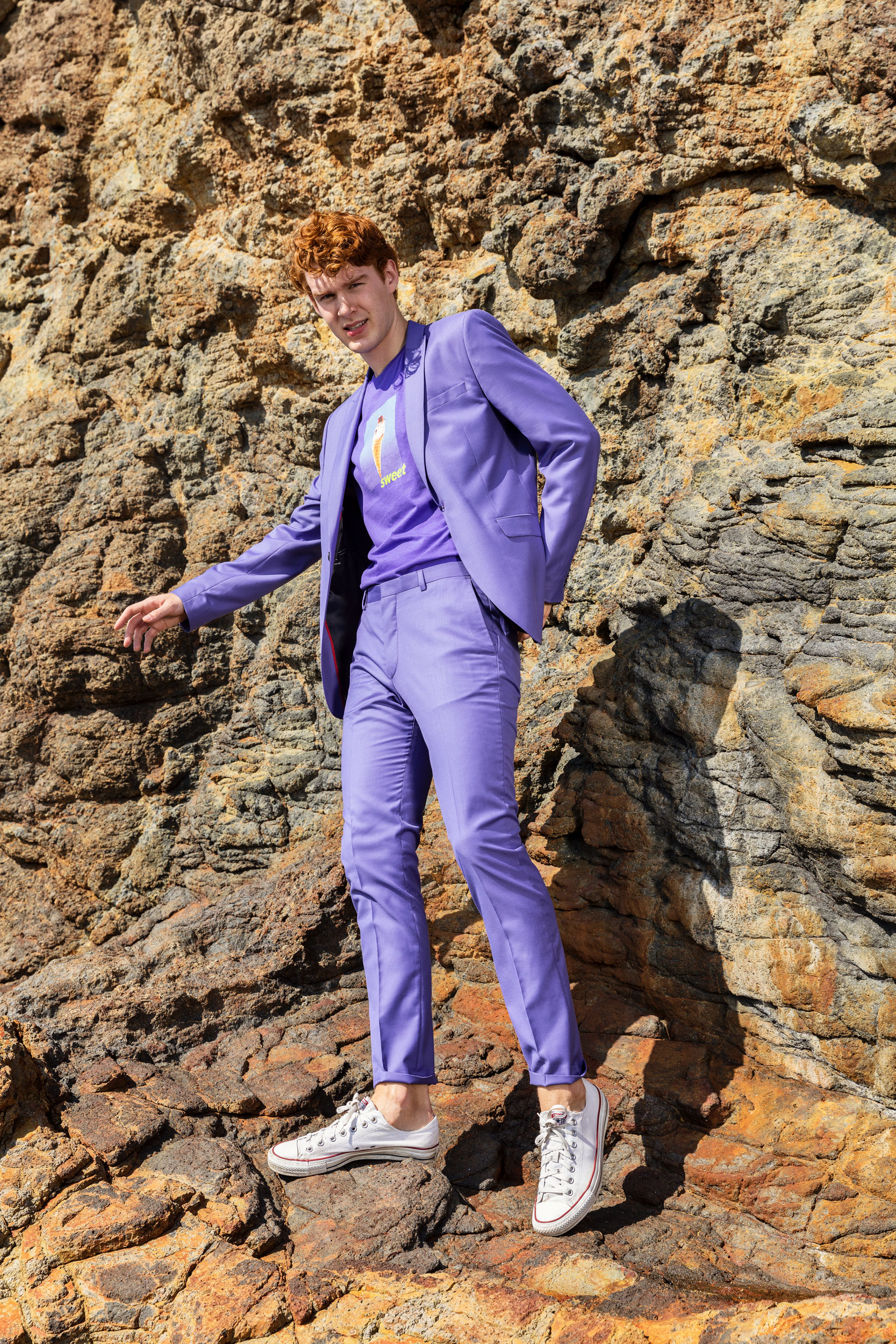 Millennial wearing a purple suit standing against a cliff