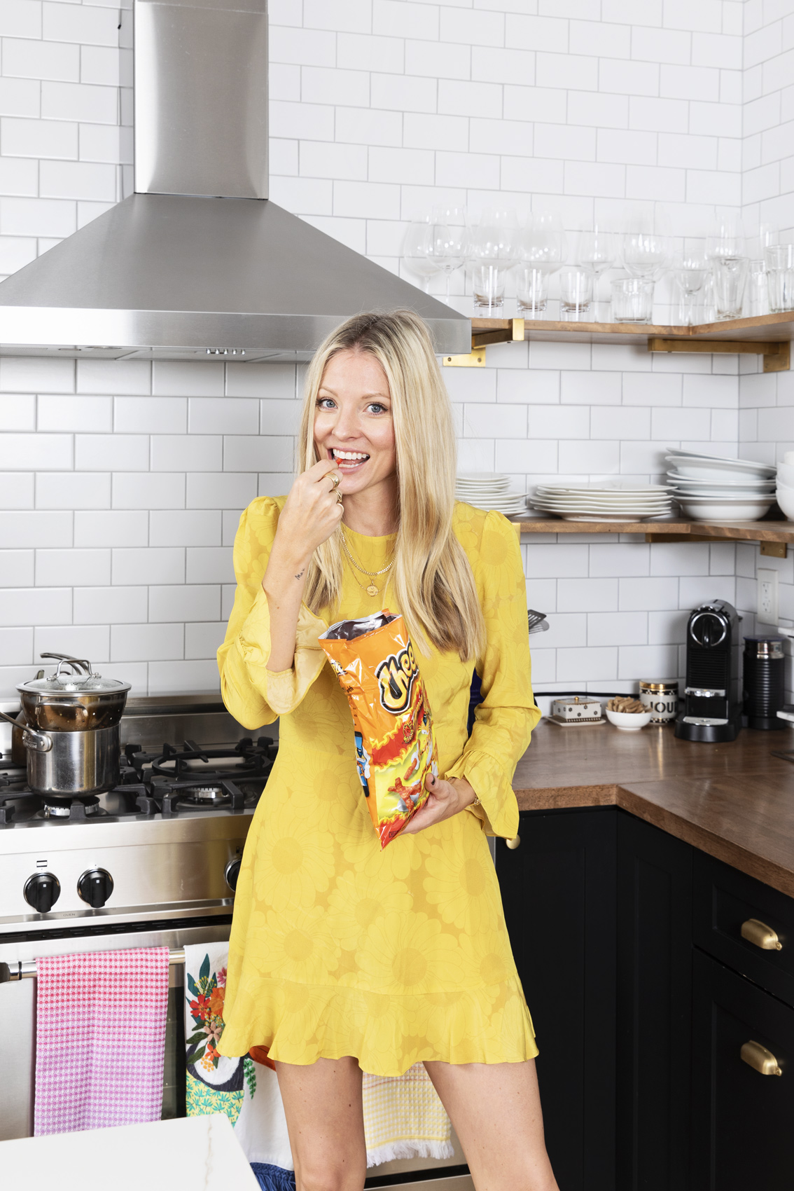 Actress Kaitlyn Doubleday standing in her home kitchen in a yellow dress