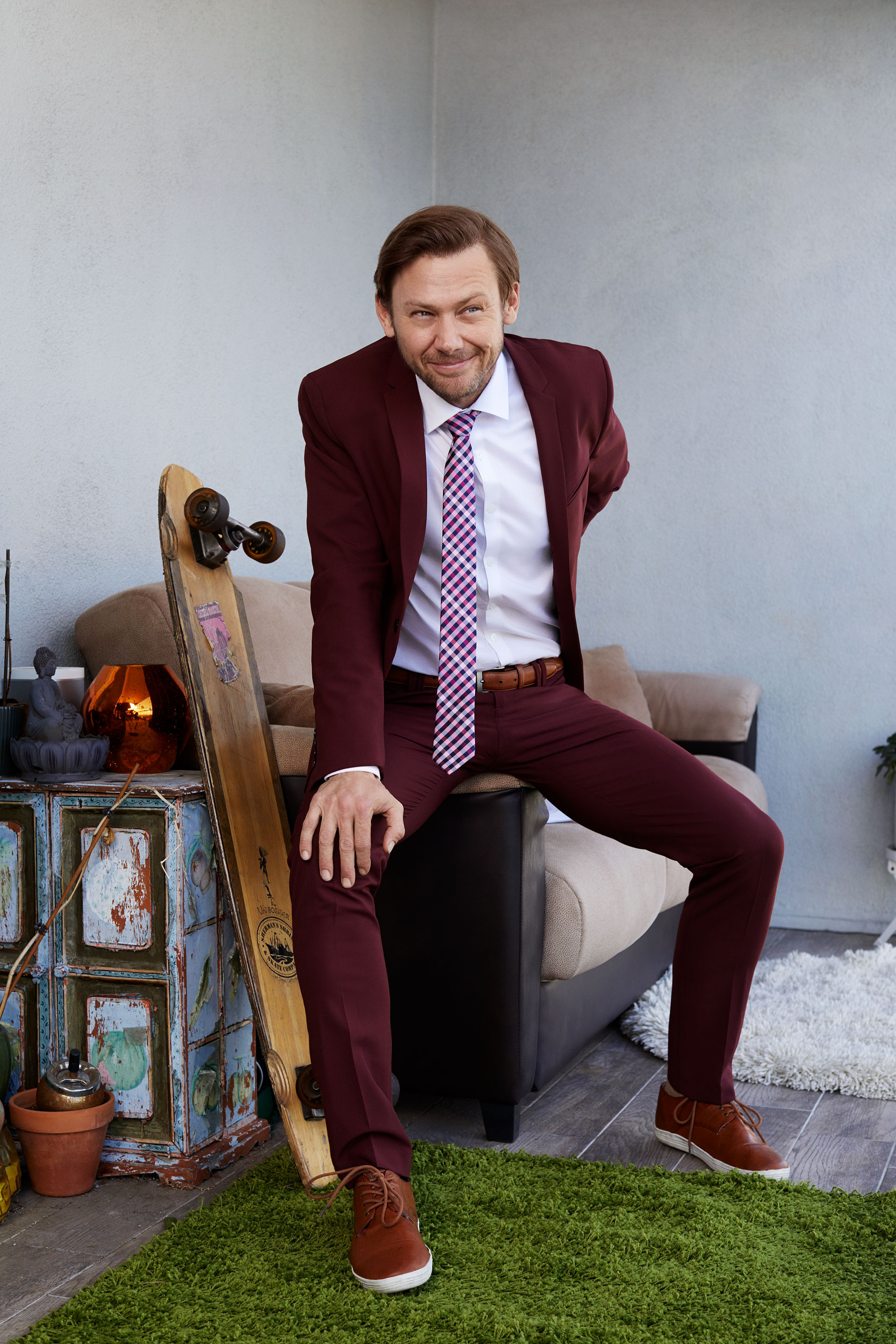 Celebrity and actor Jimmi Simpson sitting on a porch in a maroon suit. Kim Genevieve Los Angeles Portrait Photographer