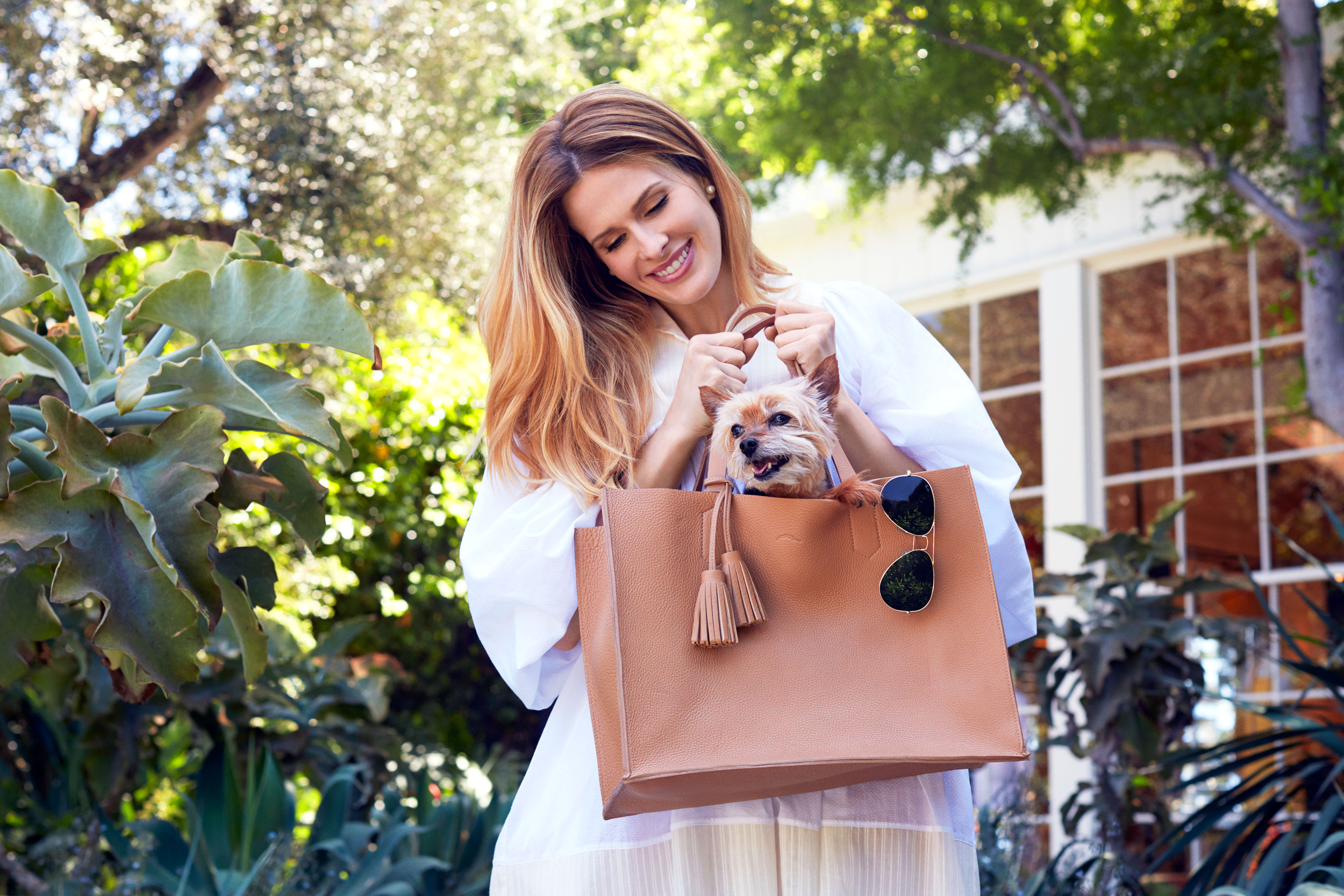 Woman in a white dress carrying her puppy in her purse. Kim Genevieve Los Angeles Portrait Photographer