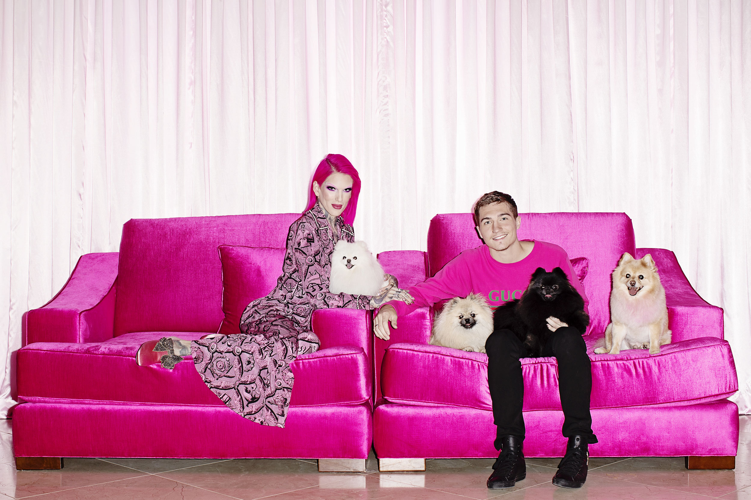 Youtube celebrity Jeffree Star sitting on a pink sofa with this dogs