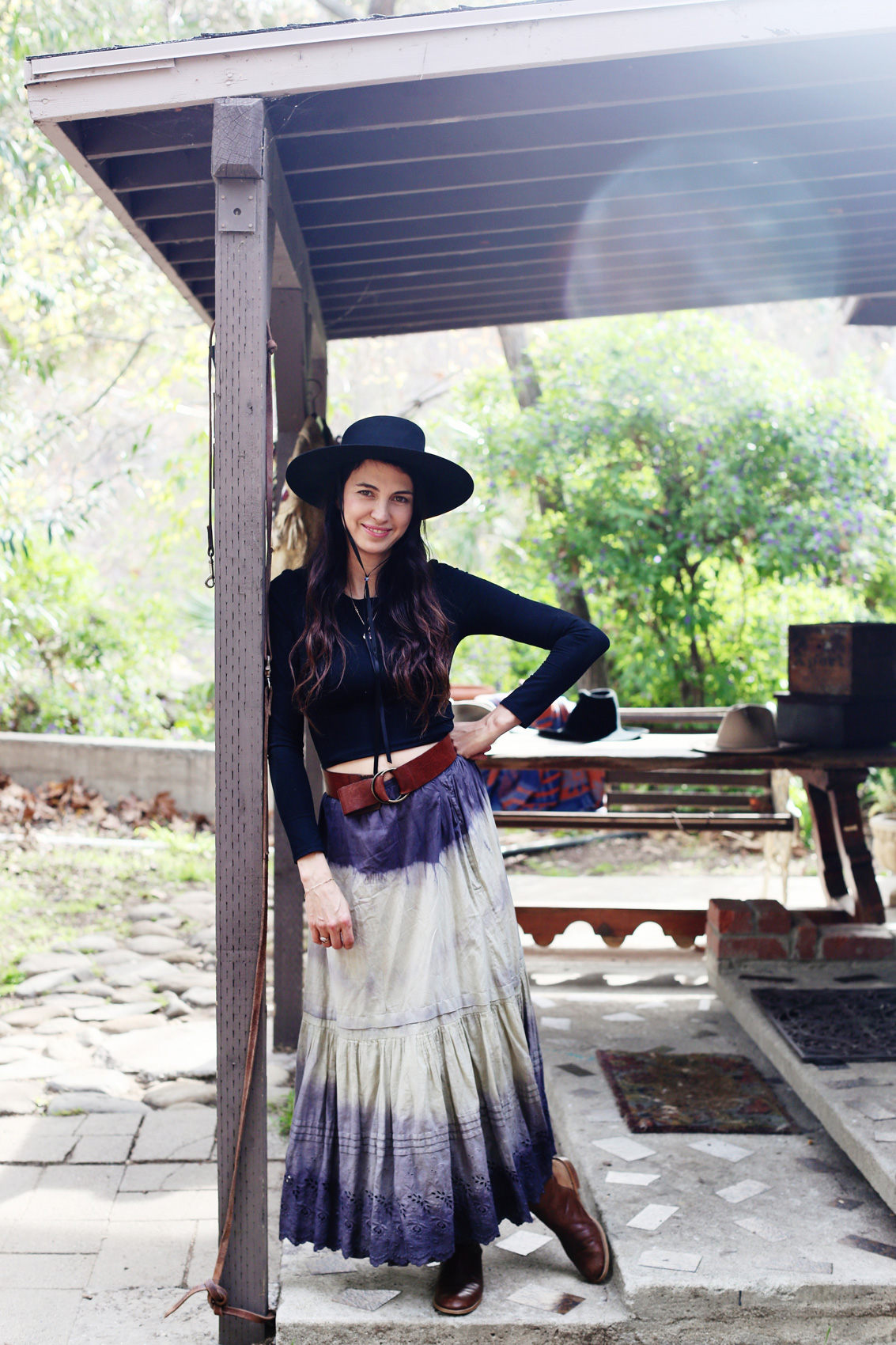Shiva Rose wearing a black hat standing on an outdoor porch