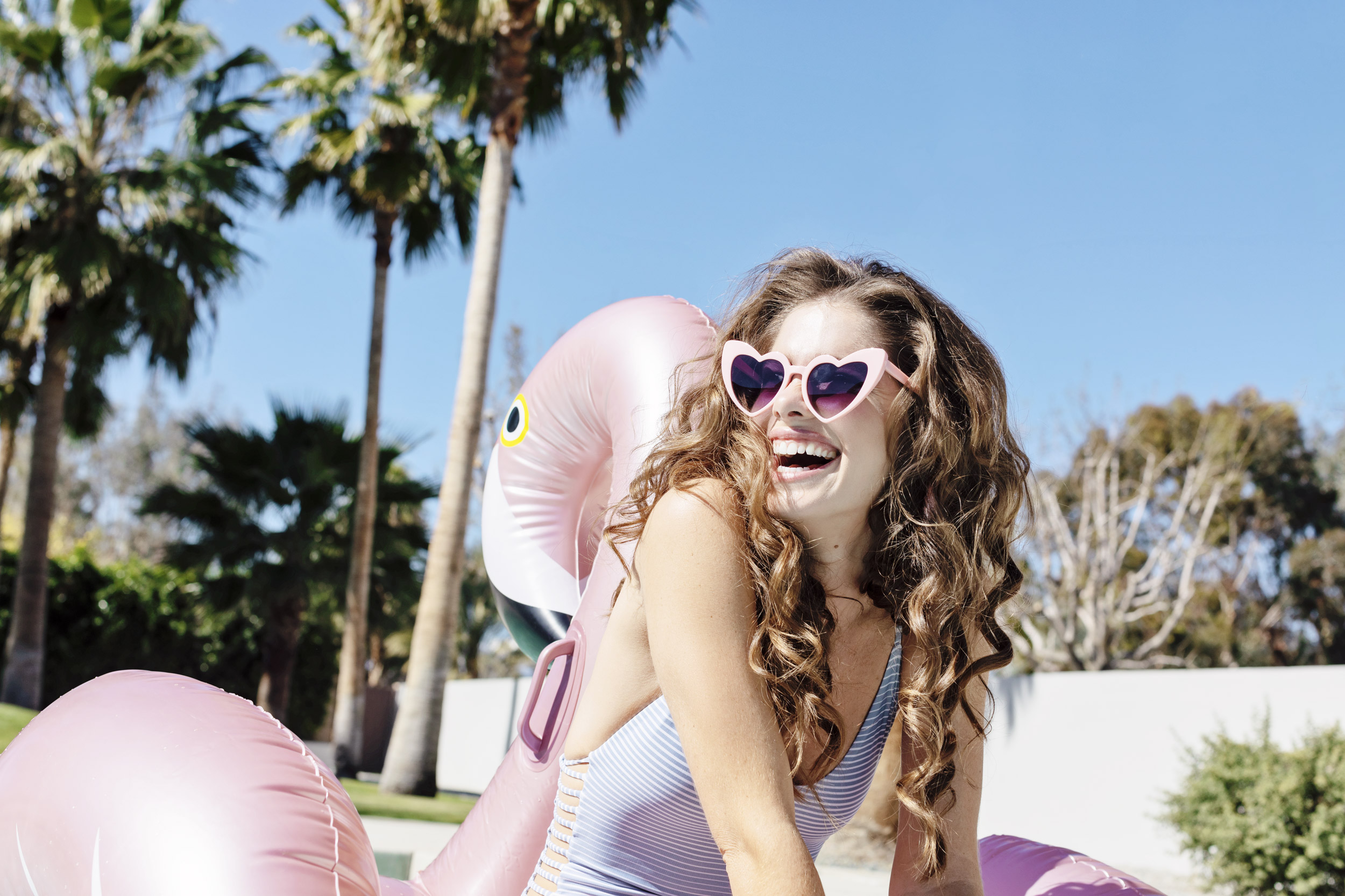Girl wearing heart sunglasses on a flamingo pool float