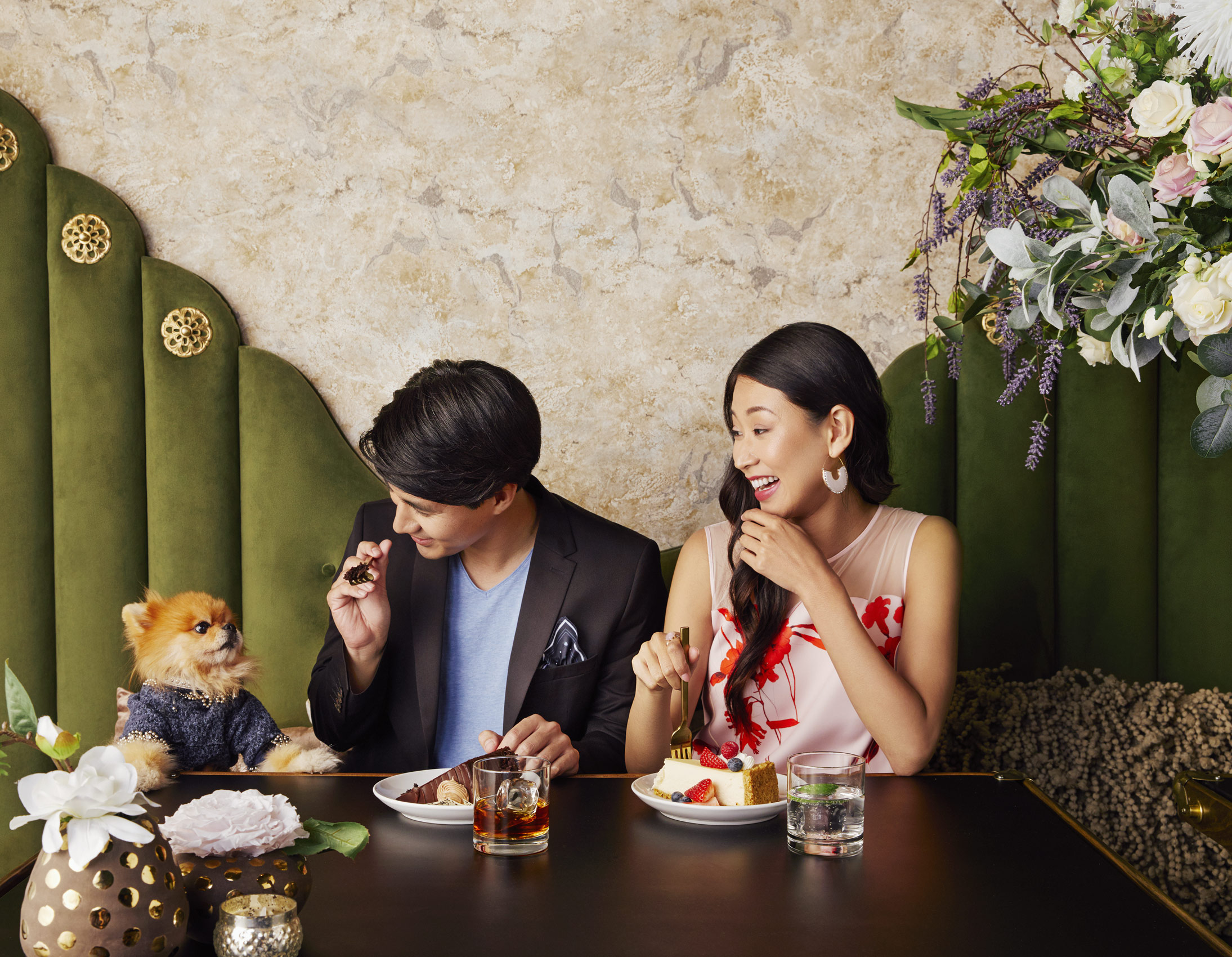 Couple feeding a puppy at a table in a restaurant - Kim Genevieve Los Angeles Lifestyle Photographer