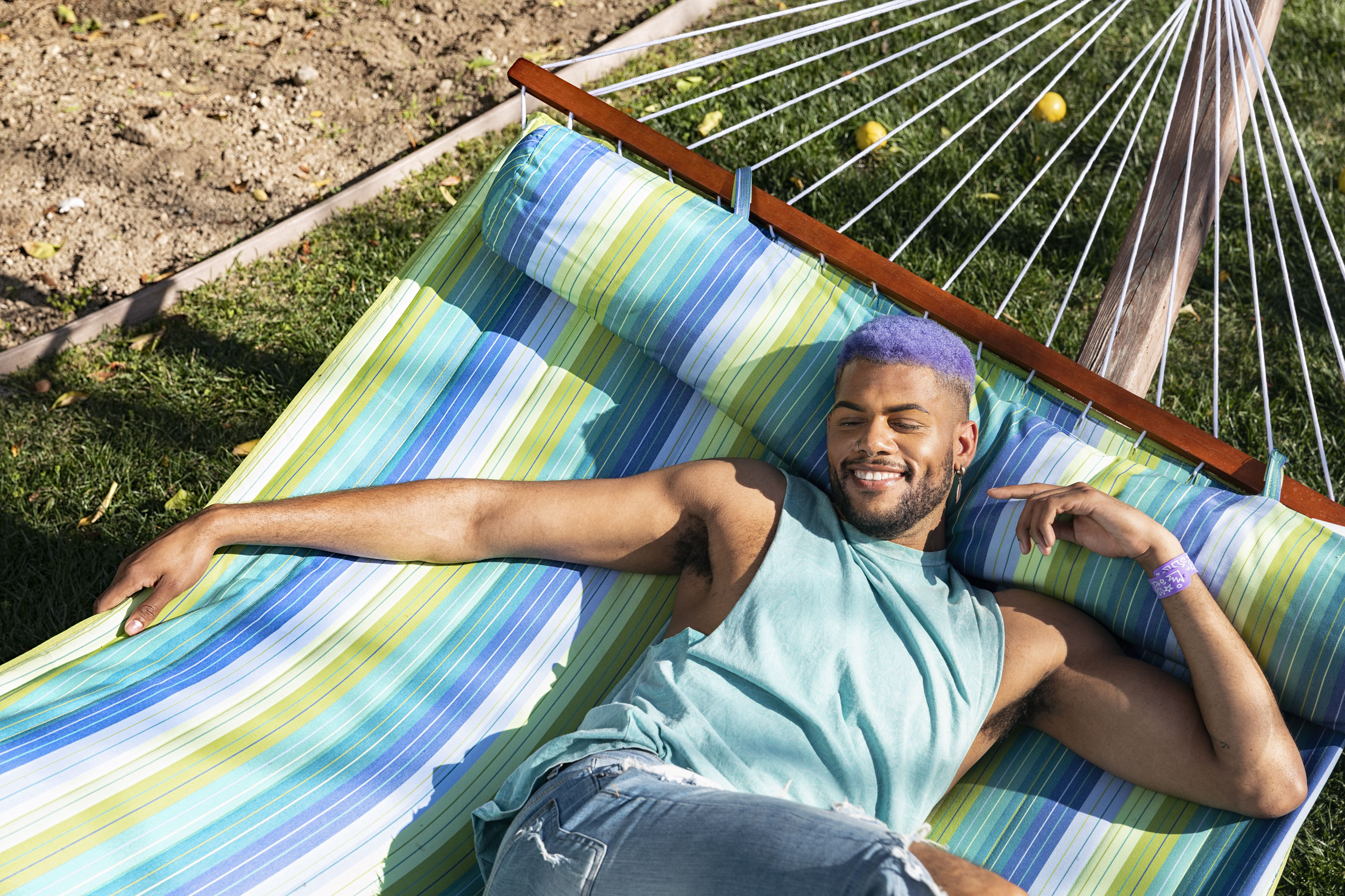 Guy with purple hair laying on a hammock smiling - Kim Genevieve Los Angeles Lifestyle Photographer
