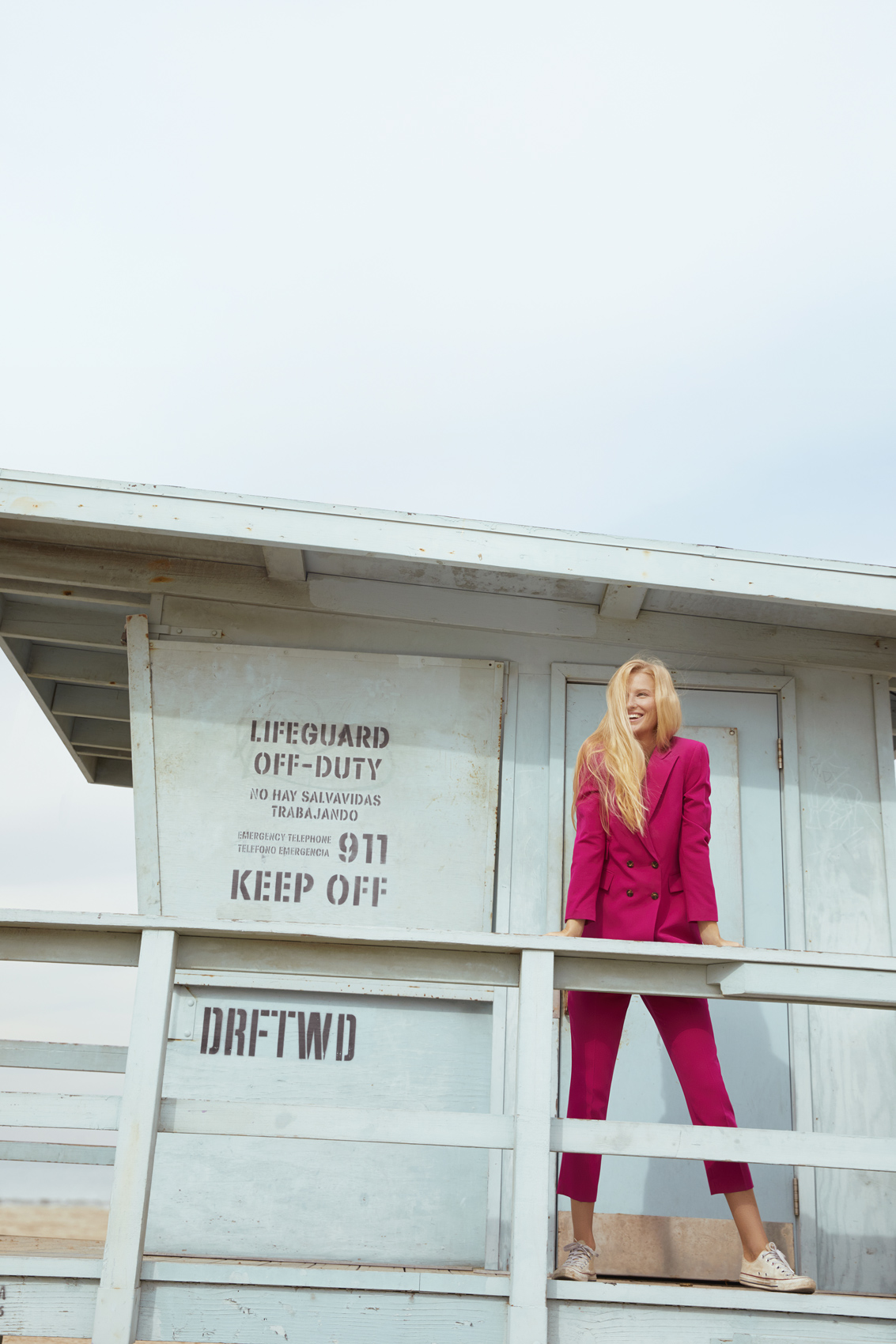 Girl in a pink suit standing on a lifeguard tower. Kim Genevieve Los Angeles Lifestyle Photographer