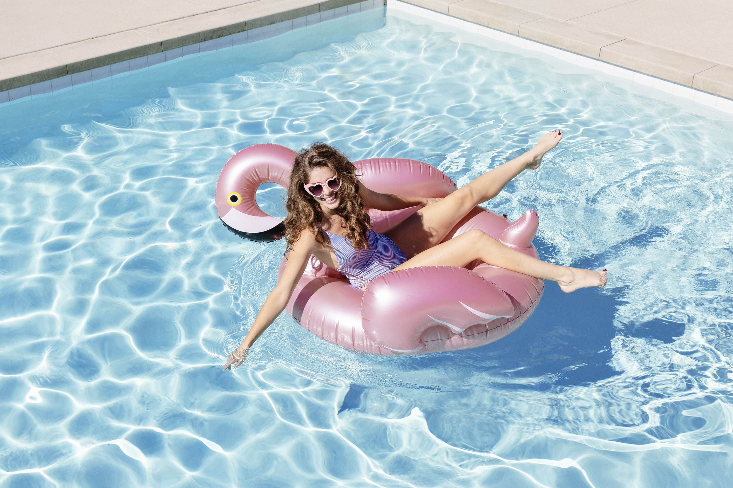 Girl wearing heart sunglasses on a flamingo pool float in a pool