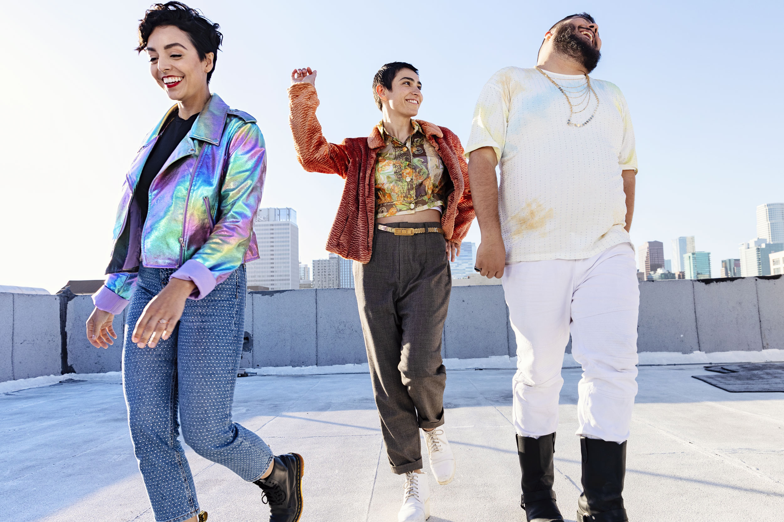 LGBTQ youth walking together laughing on a city roof