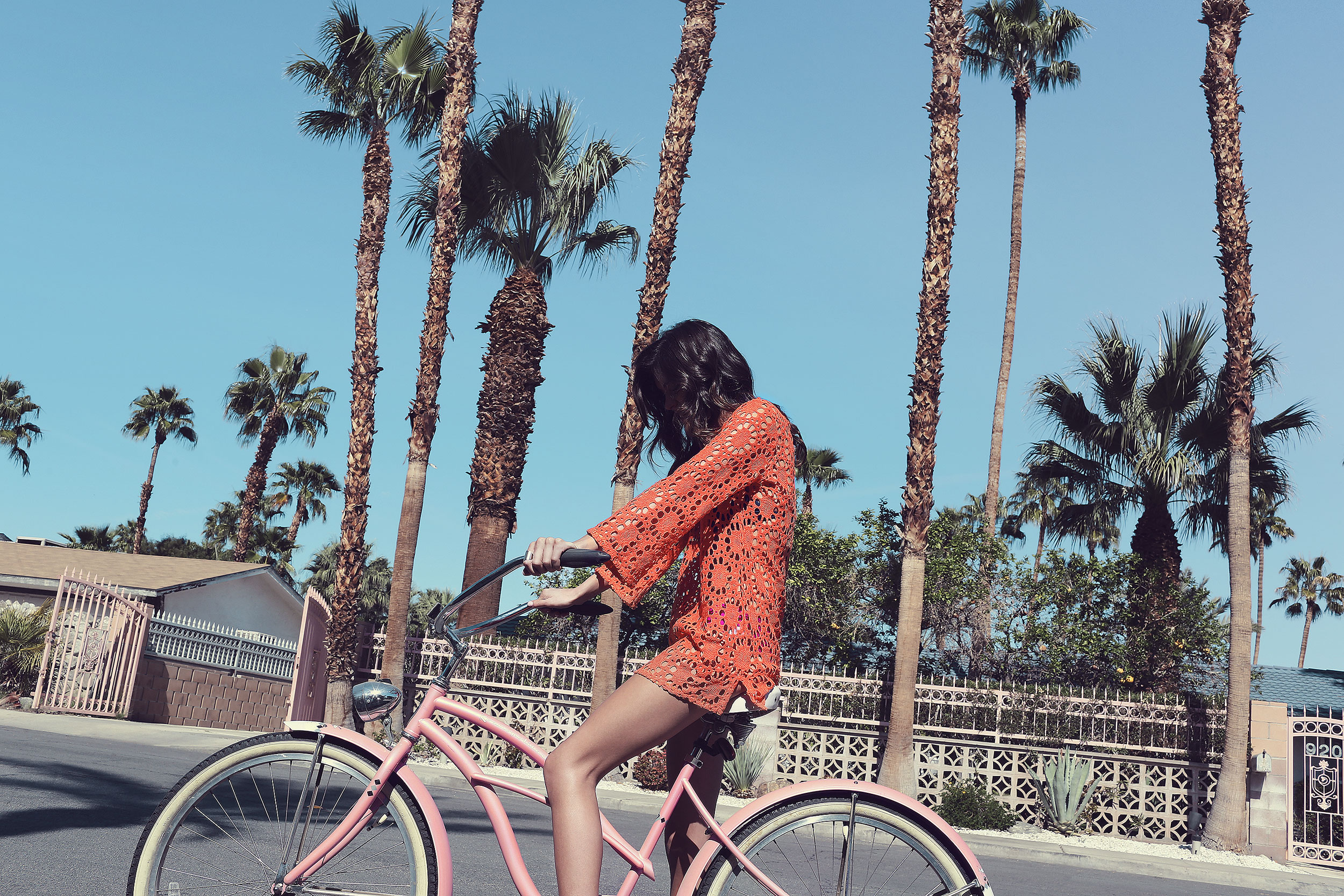 Brunette on a pink beach cruiser wearing an orange coverup - Kim Genevieve Los Angeles Lifestyle Photographer