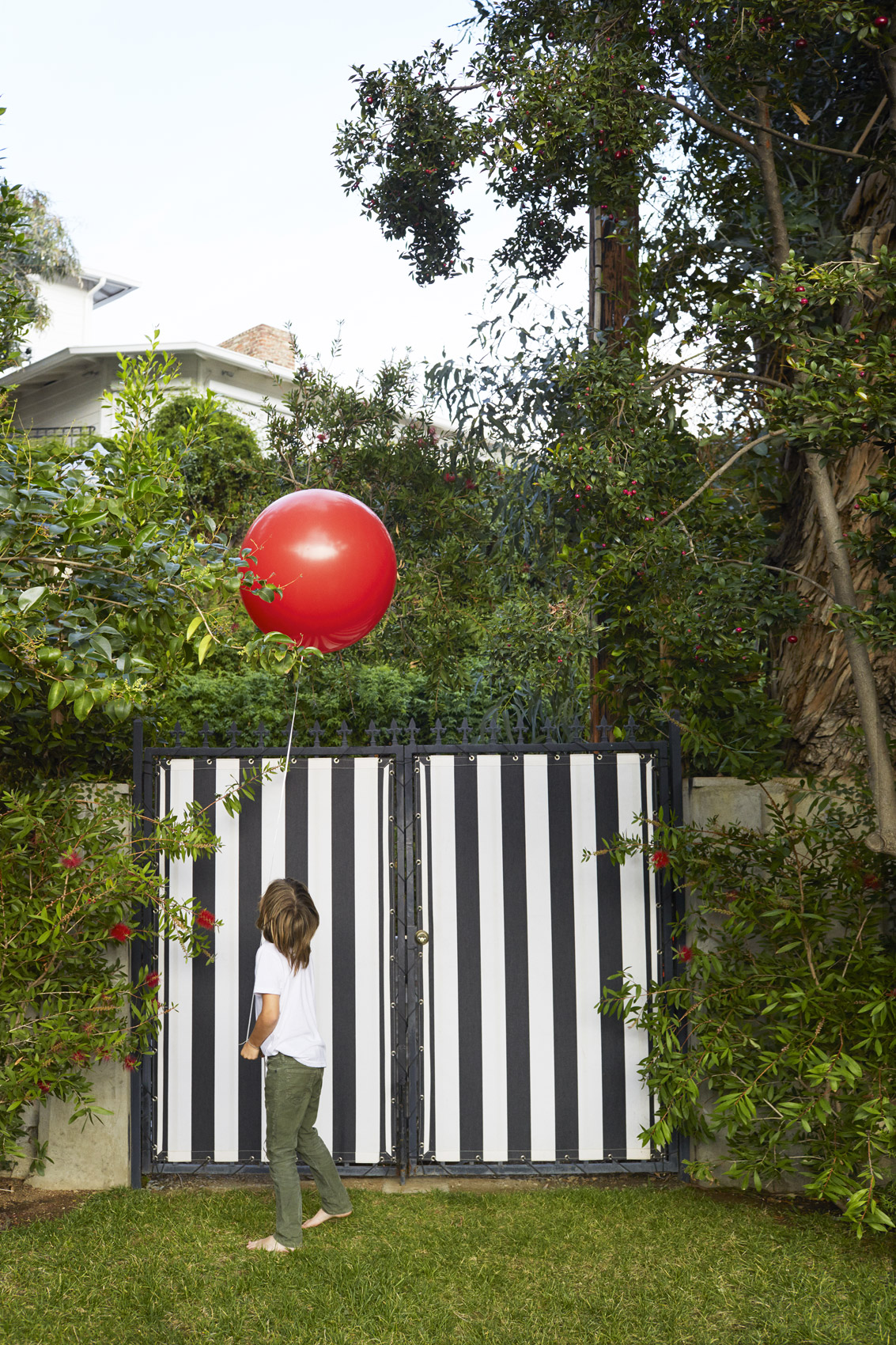 Kid in a backyard holding a big red balloon - Kim Genevieve Los Angeles Lifestyle Photographer
