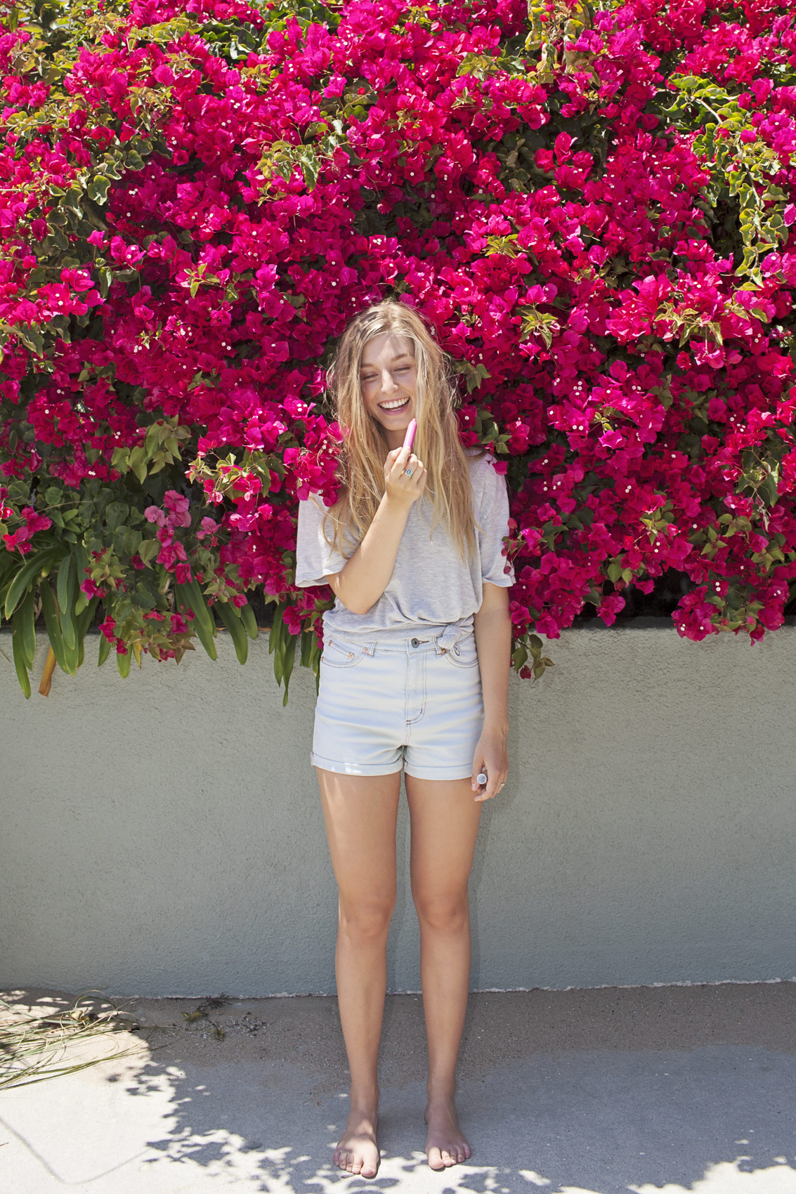 Smiling girl with blonde hair putting lipstick on outside. Kim Genevieve Los Angeles Lifestyle Photographer