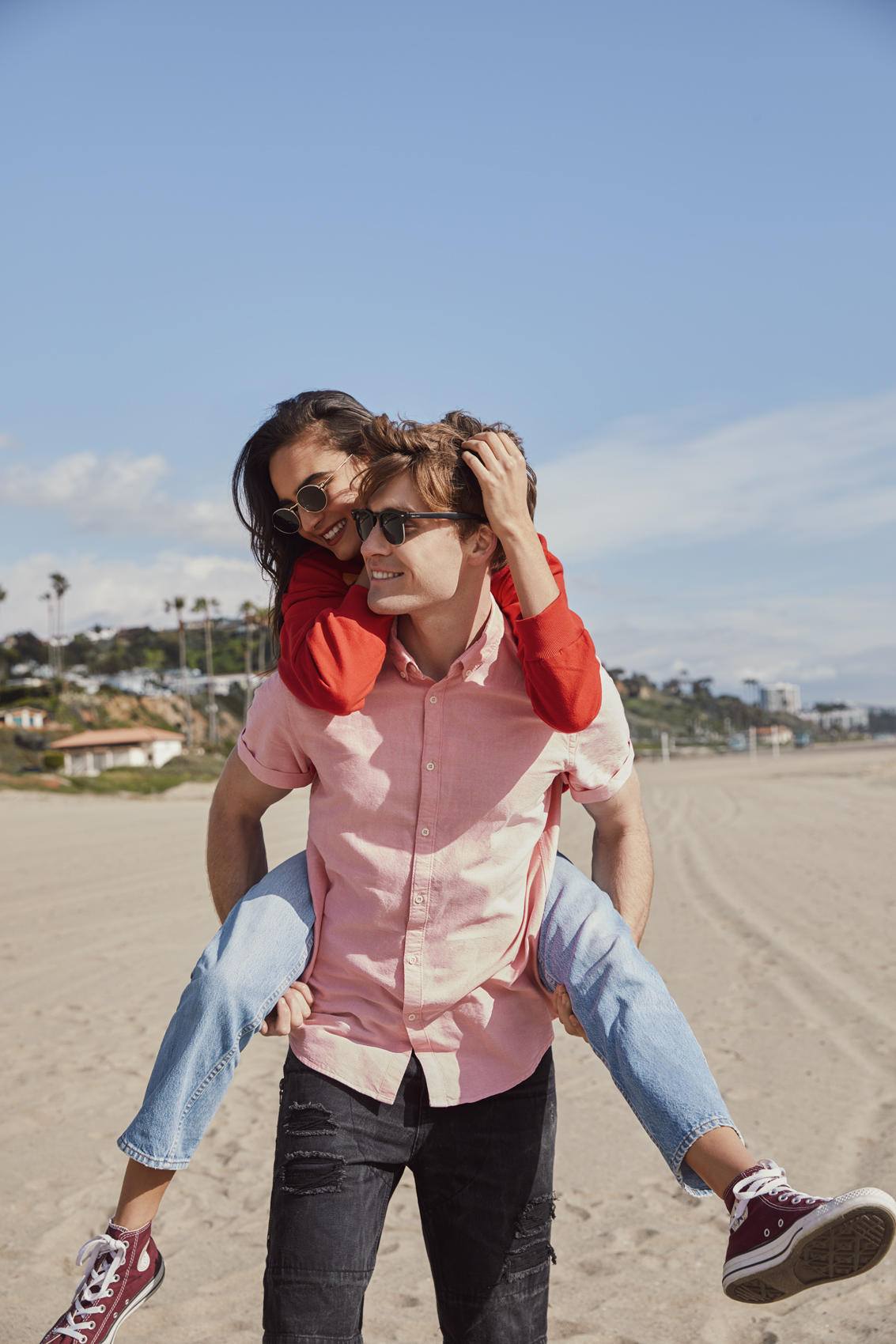Guy giving a girl a piggy back ride on the beach. Kim Genevieve Los Angeles Lifestyle Photographer