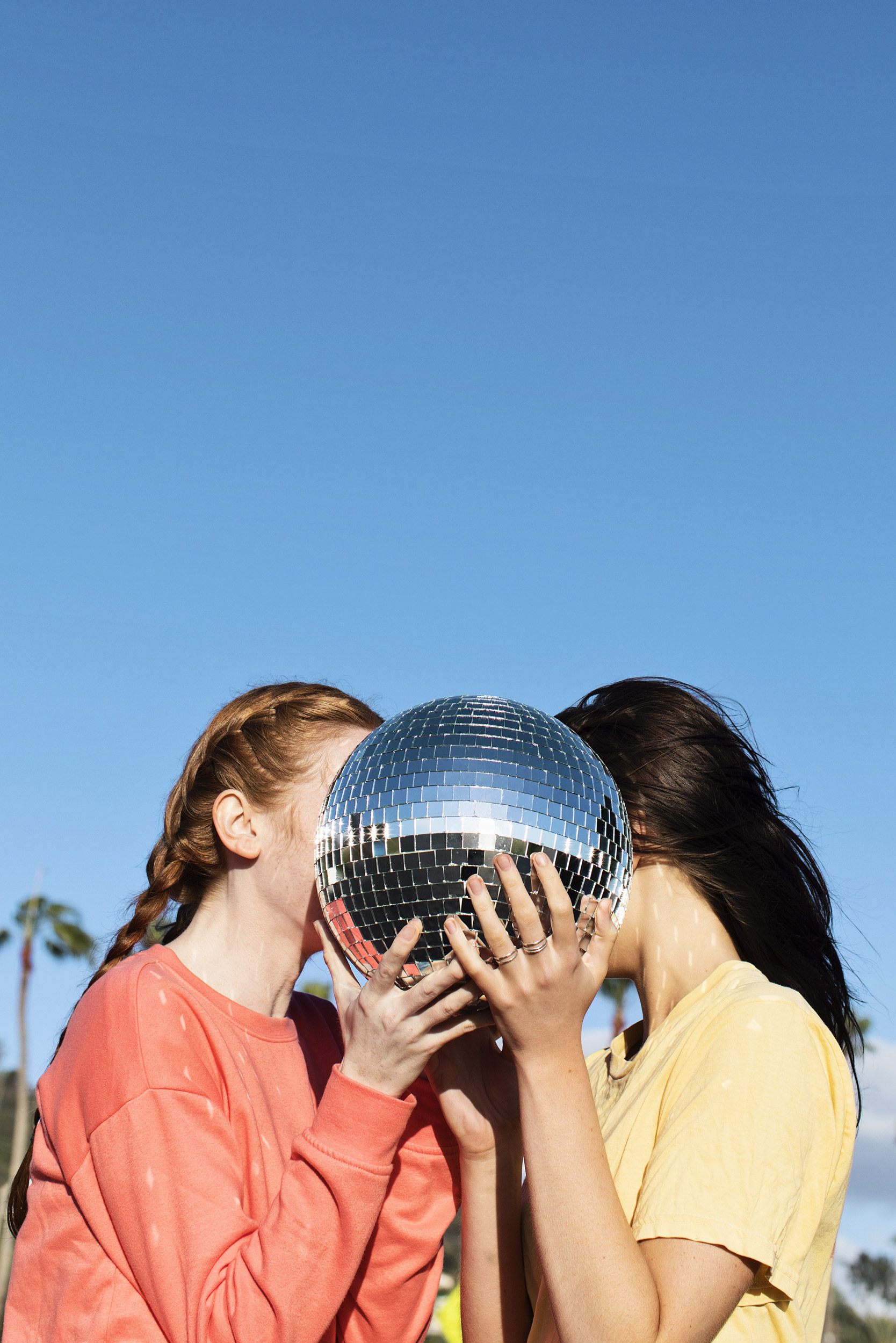Two girls hiding their face behind a disco ball