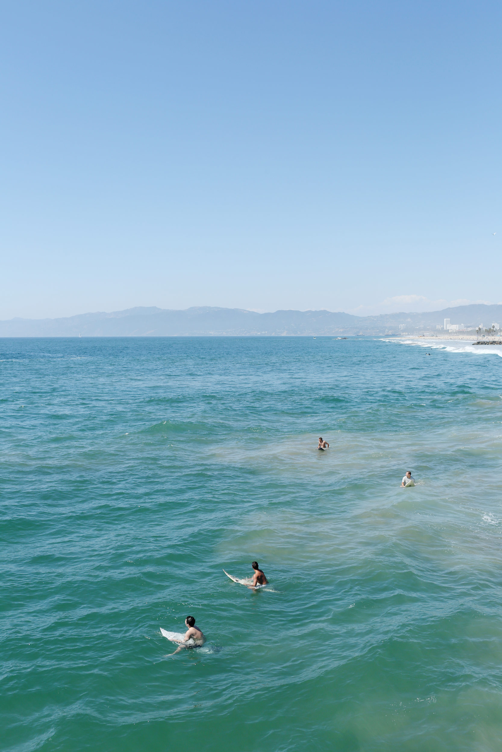 Surfers in the ocean. Kimberly Genevieve lifestyle photographer Los Angeles